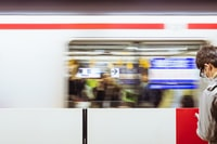 A blurry shot of a moving train in front of a man at the Tokyo Station.