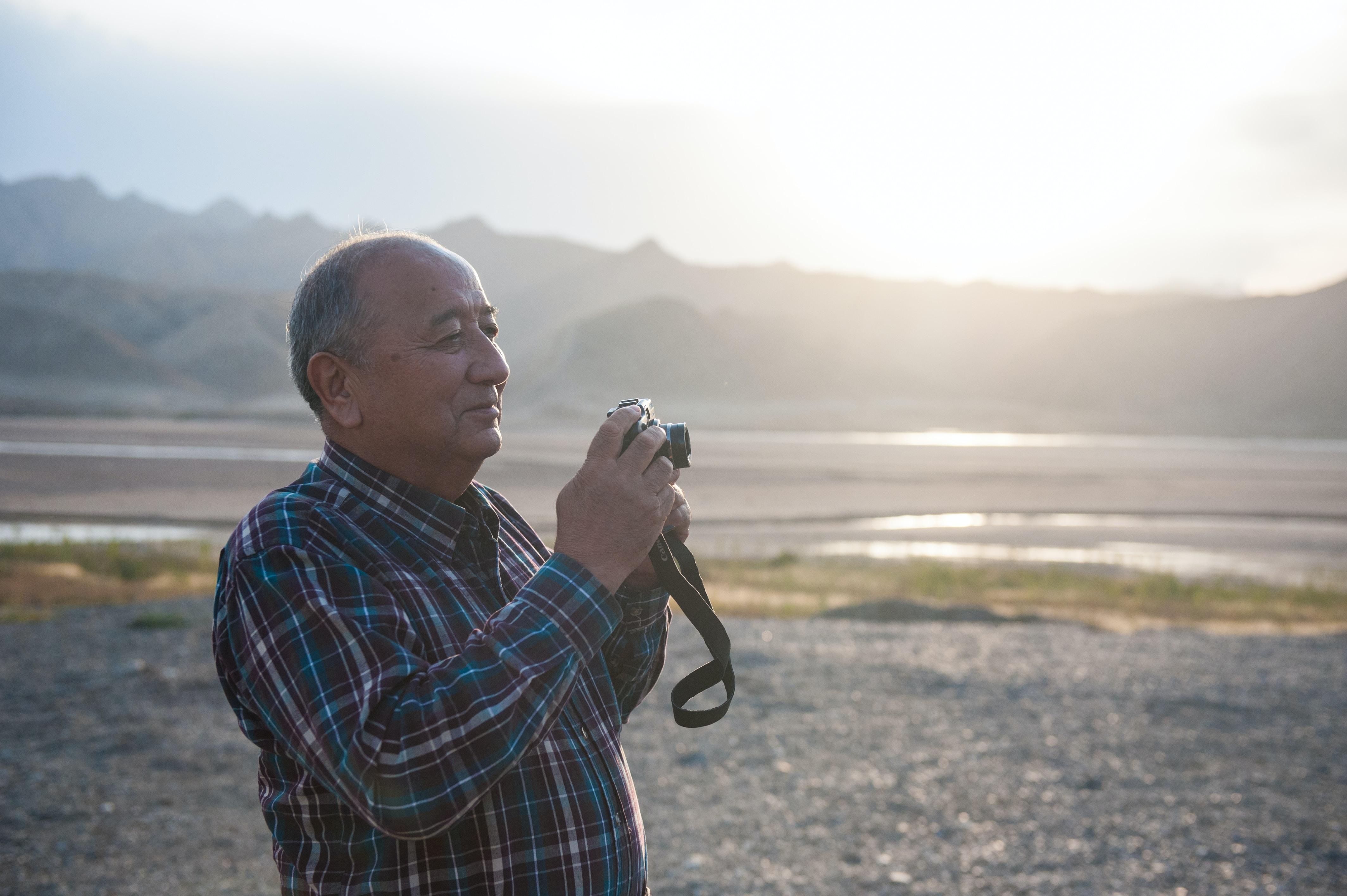 Old man in checkered shirt holding a photo camera at Torgayti Village