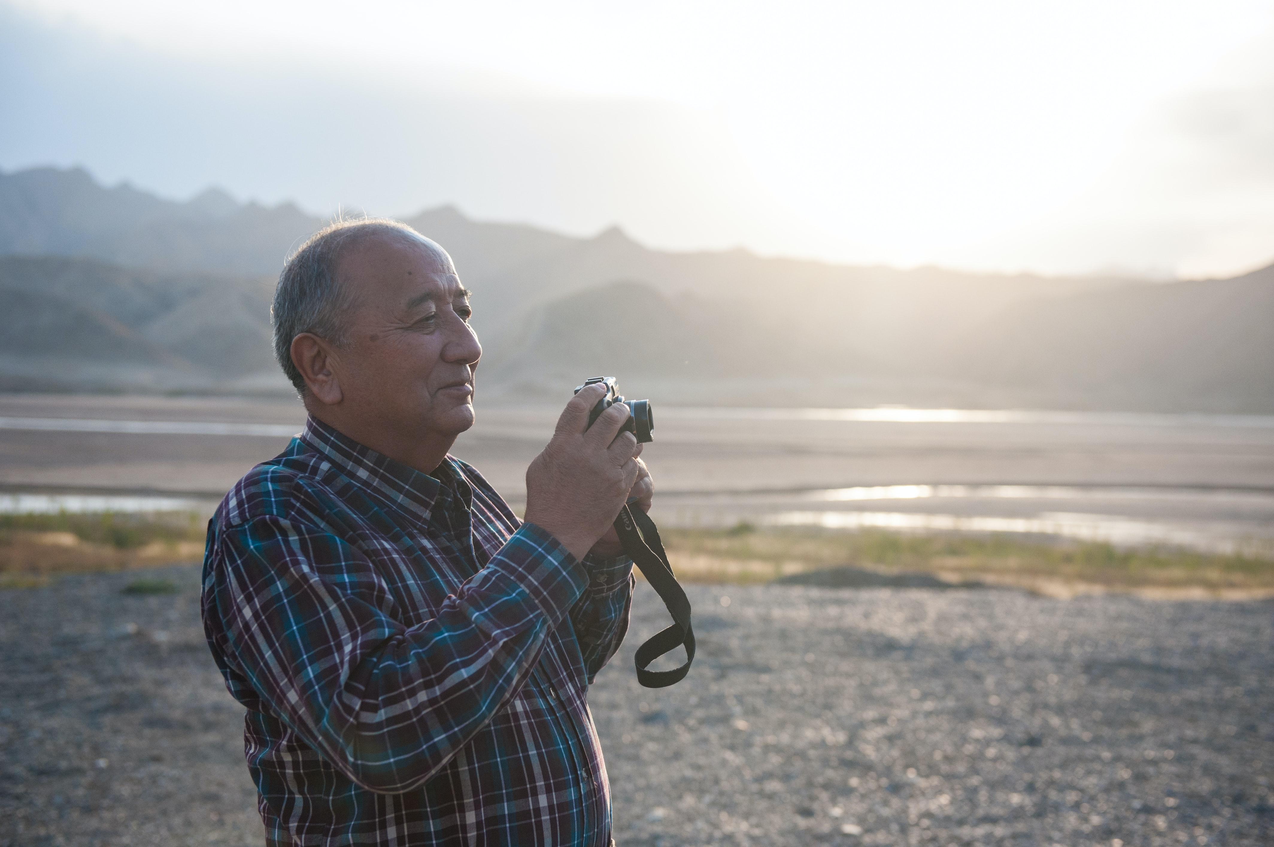 man holding camera standing with mountain background