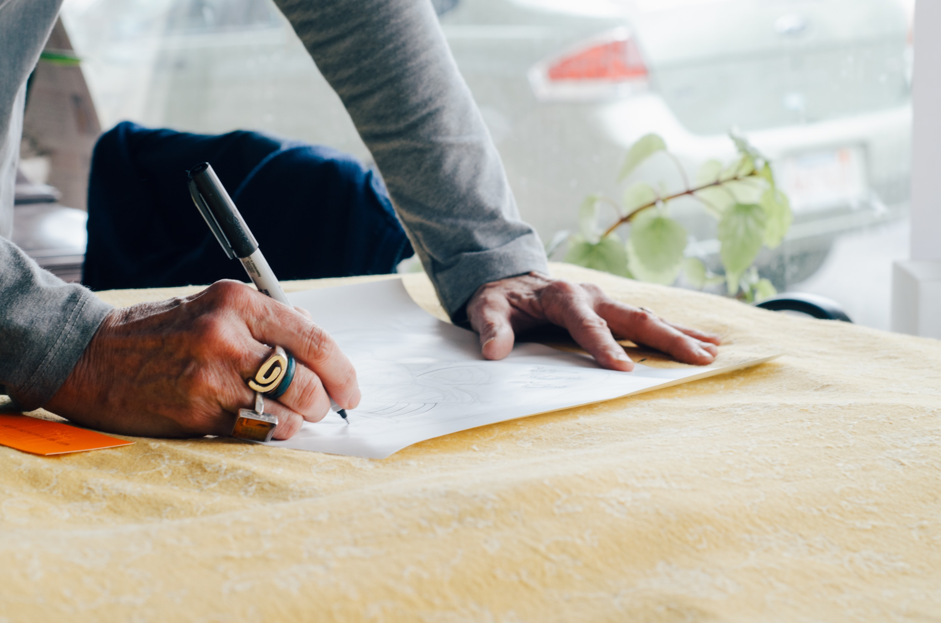 person writing on white plain paper on the table photography