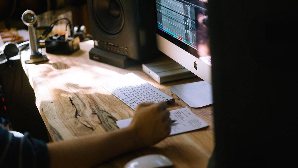 person using silver iMac, Apple Magic Keyboard, and Magic Mouse set