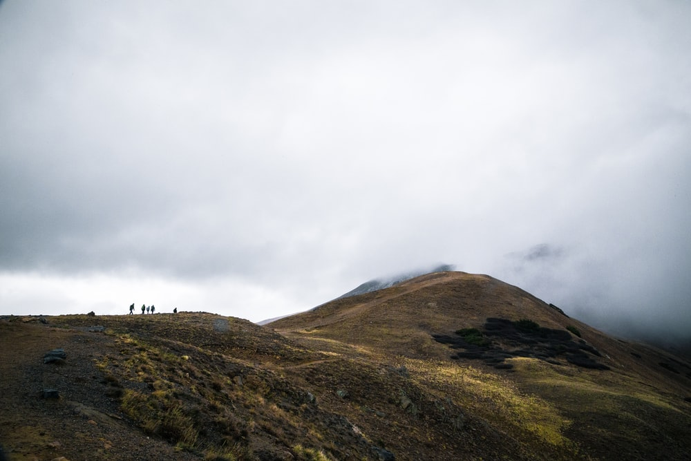 silhouette of people on mountain cliff facing fogs