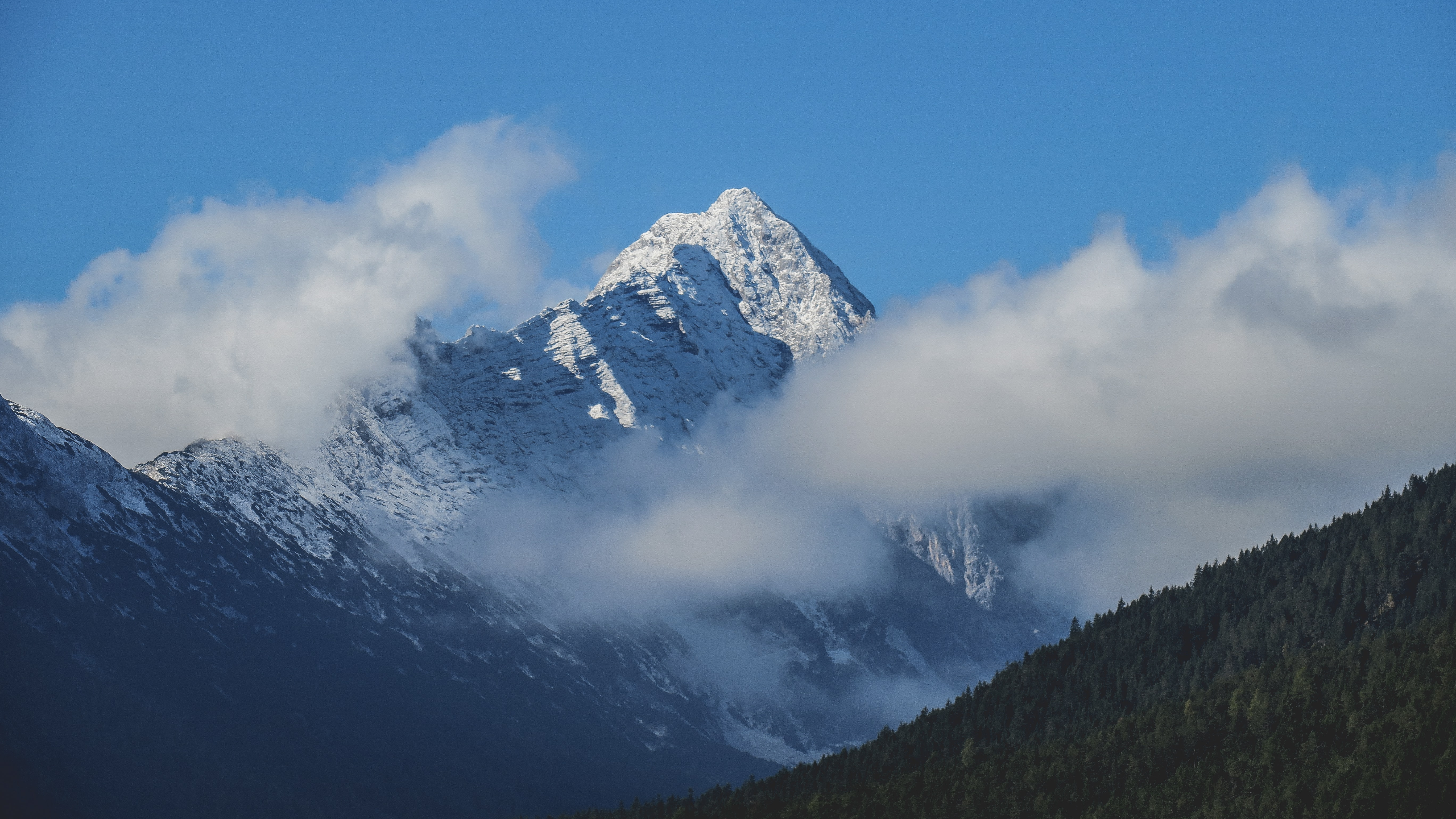 A snowy mountain peak rising up between thick clouds in Leutasch