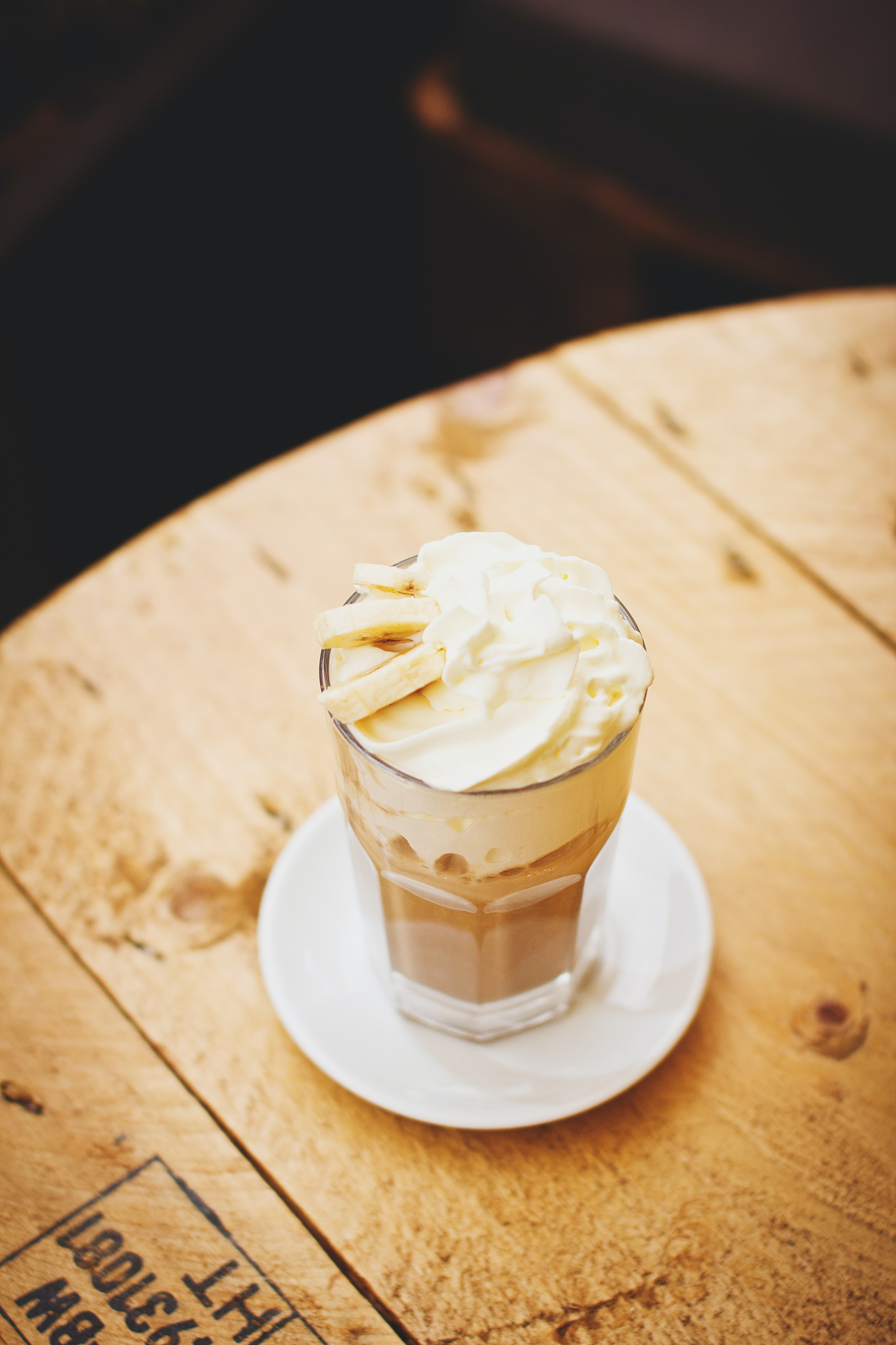 Coffee drink with whipped cream and banana sits on a cafe table