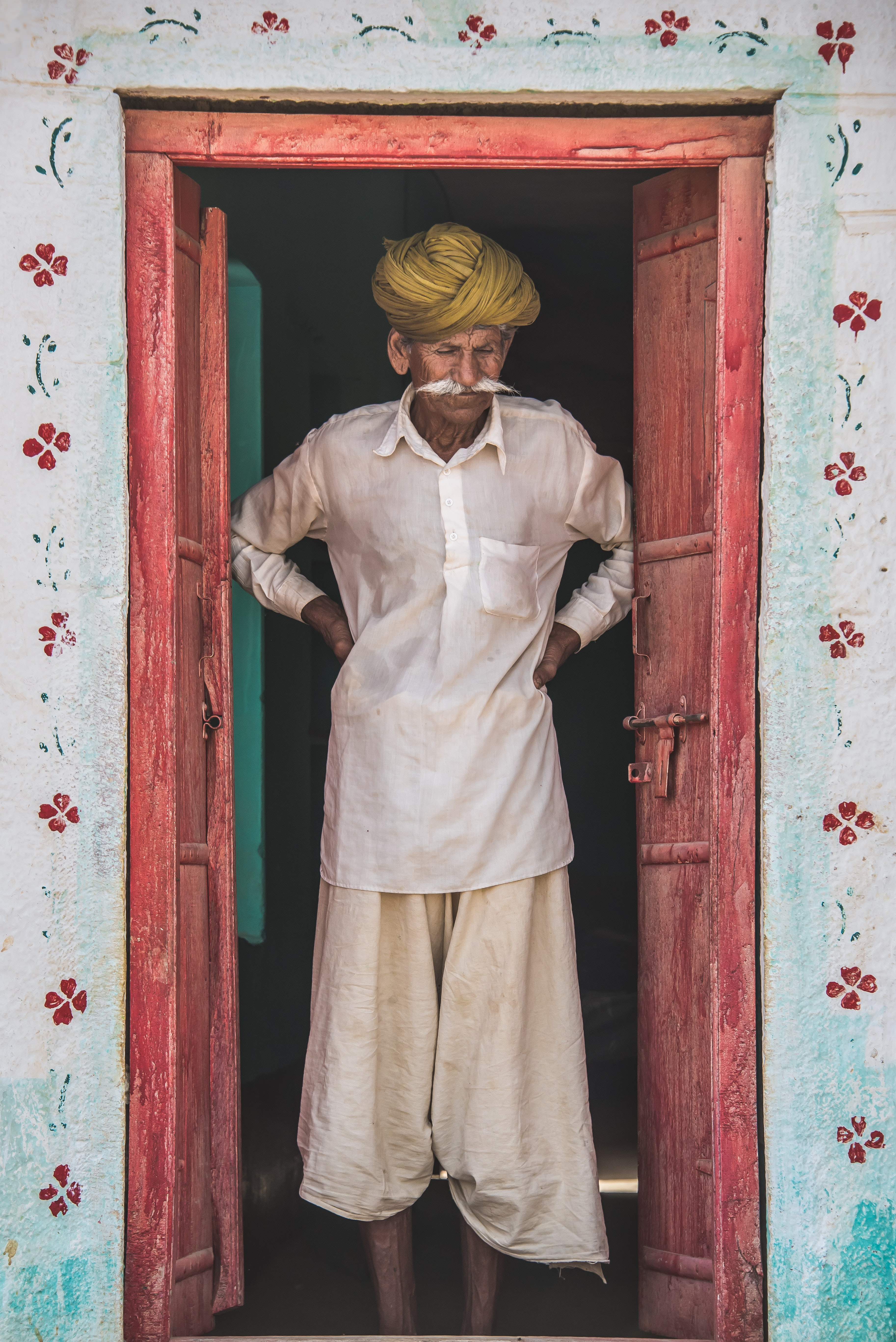 Indian man with flowy clothes and a yellow turban standing in a pink doorway with flower wallpaper on the walls