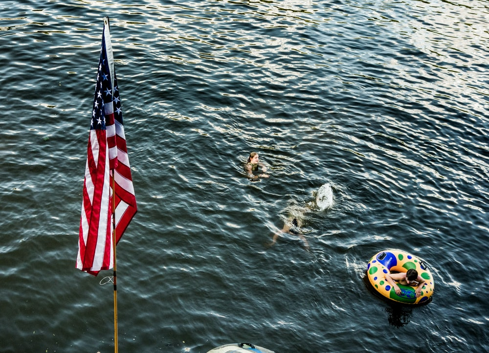 three person swimming in body of water near US flag