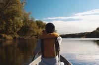 person wearing flotation vest rowing boat