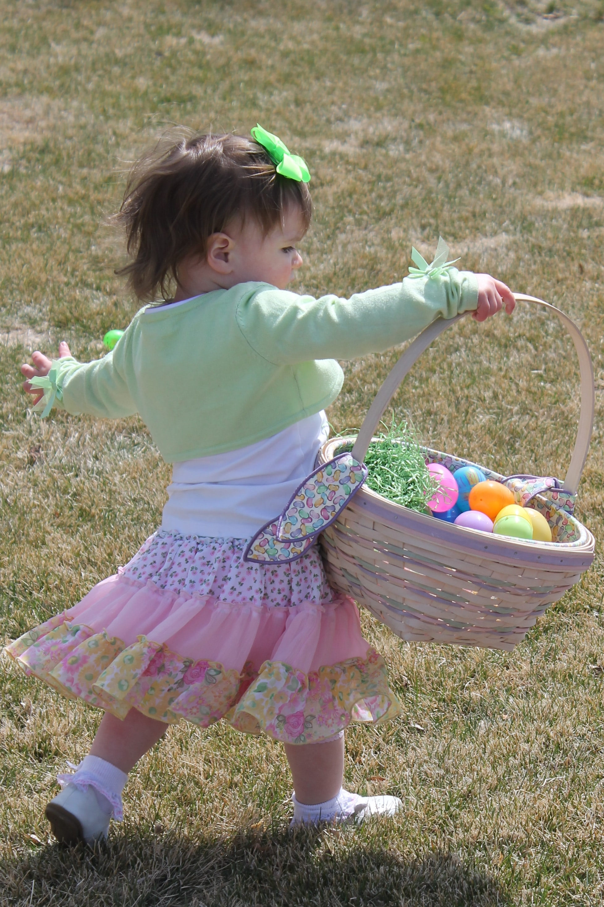 A girl carrying plastic eggs in an Easter basket.