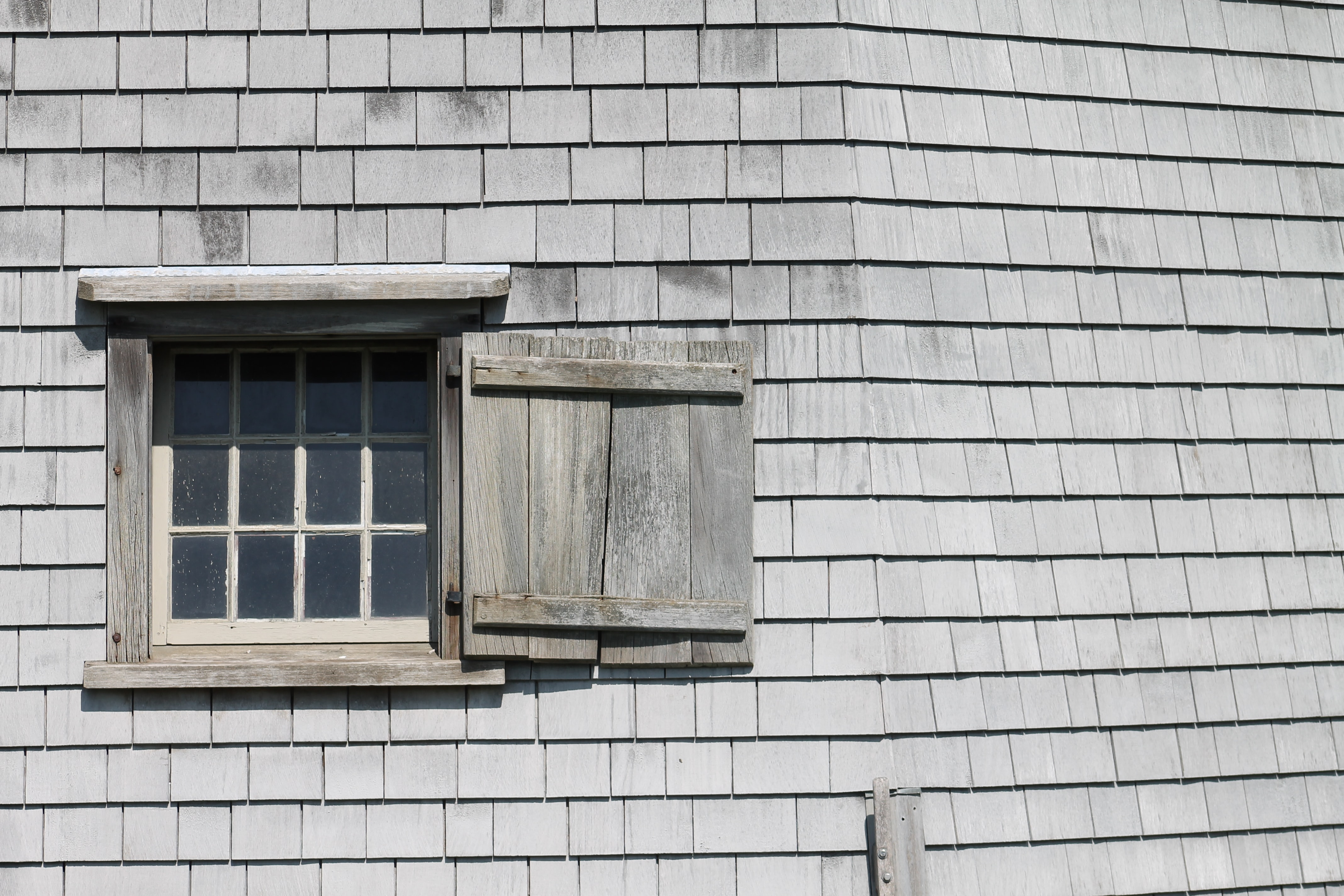 A rustic window with a wooden shutter in a roof