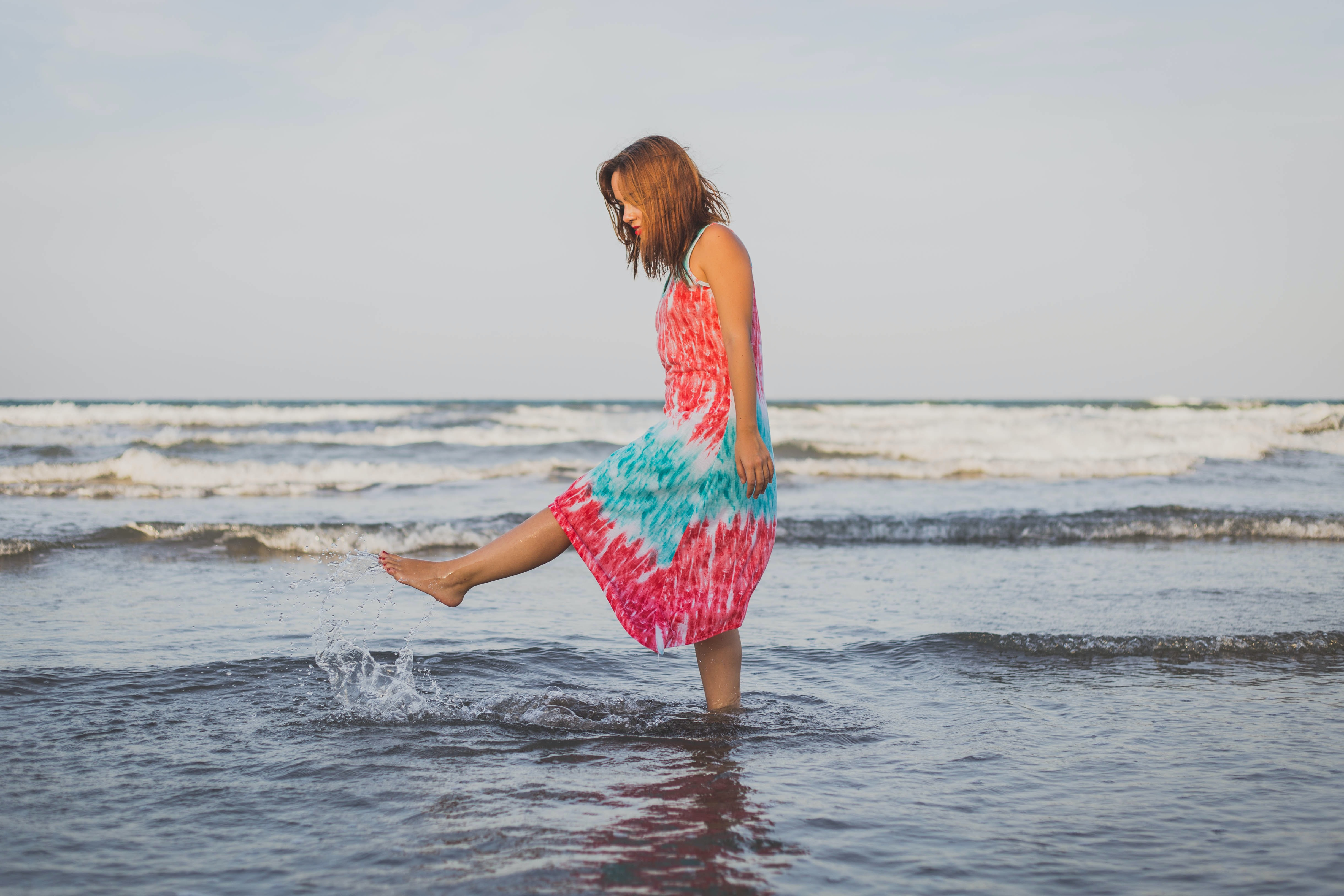 Woman in a colorful dress kicks water and plays in ocean waves