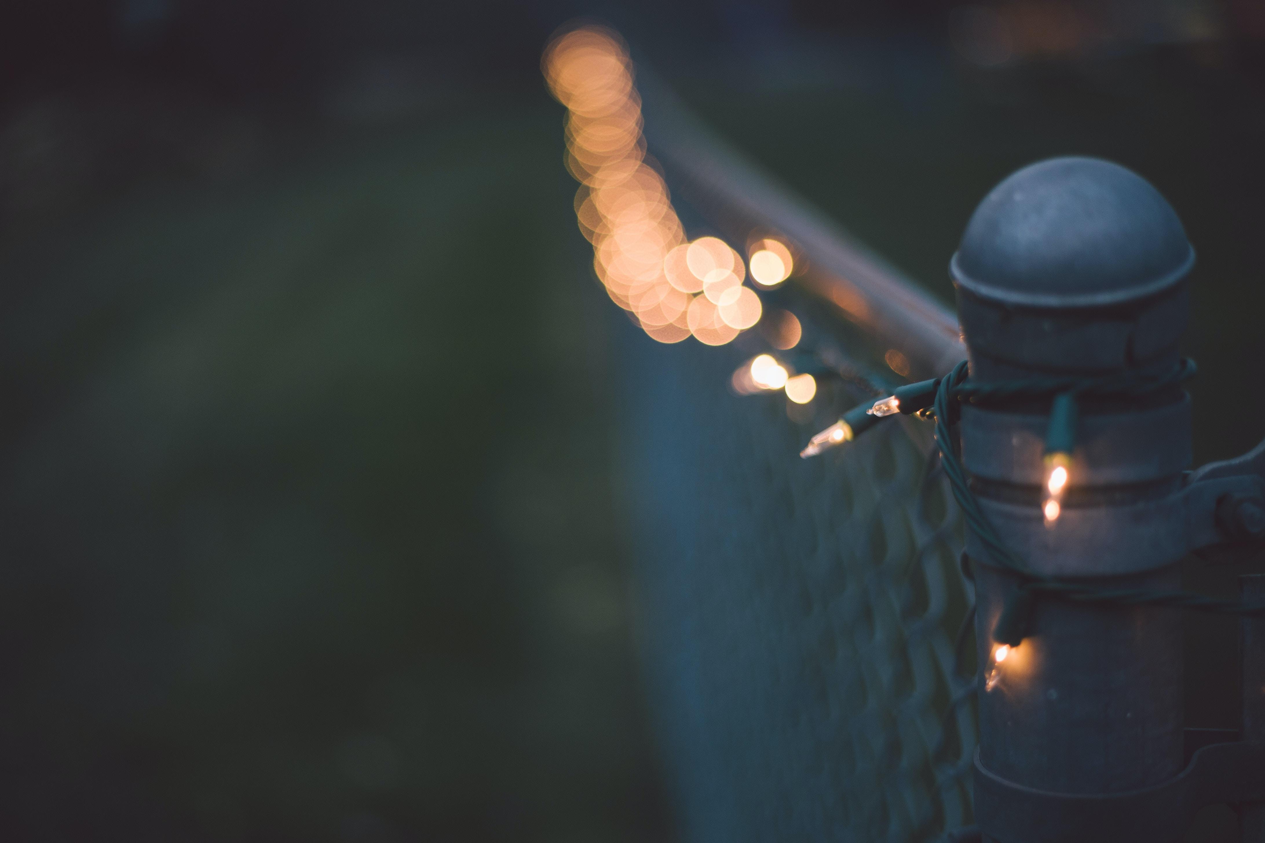 Metal fence post with bokeh string of Christmas lights