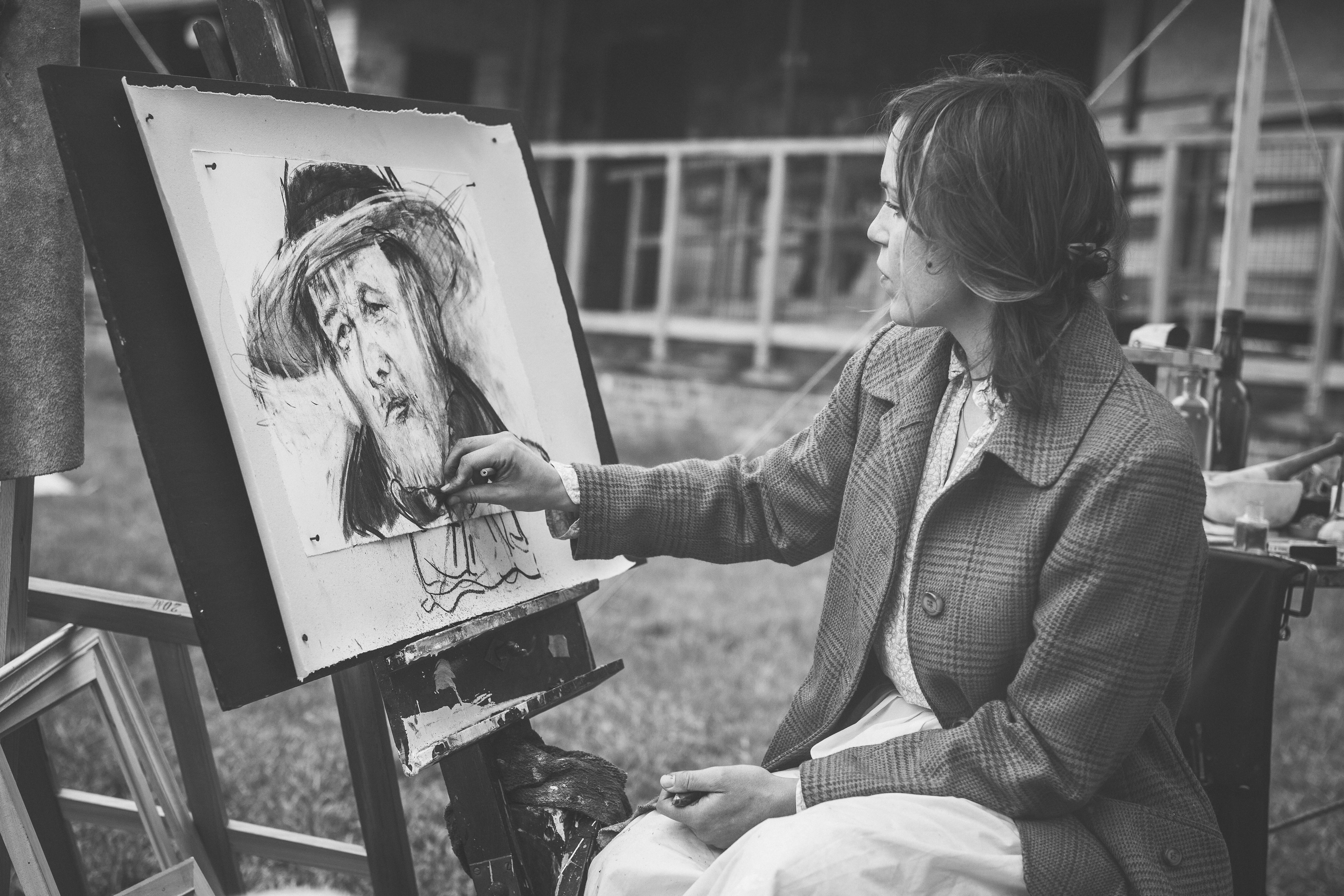 grayscale photography of woman sitting while painting