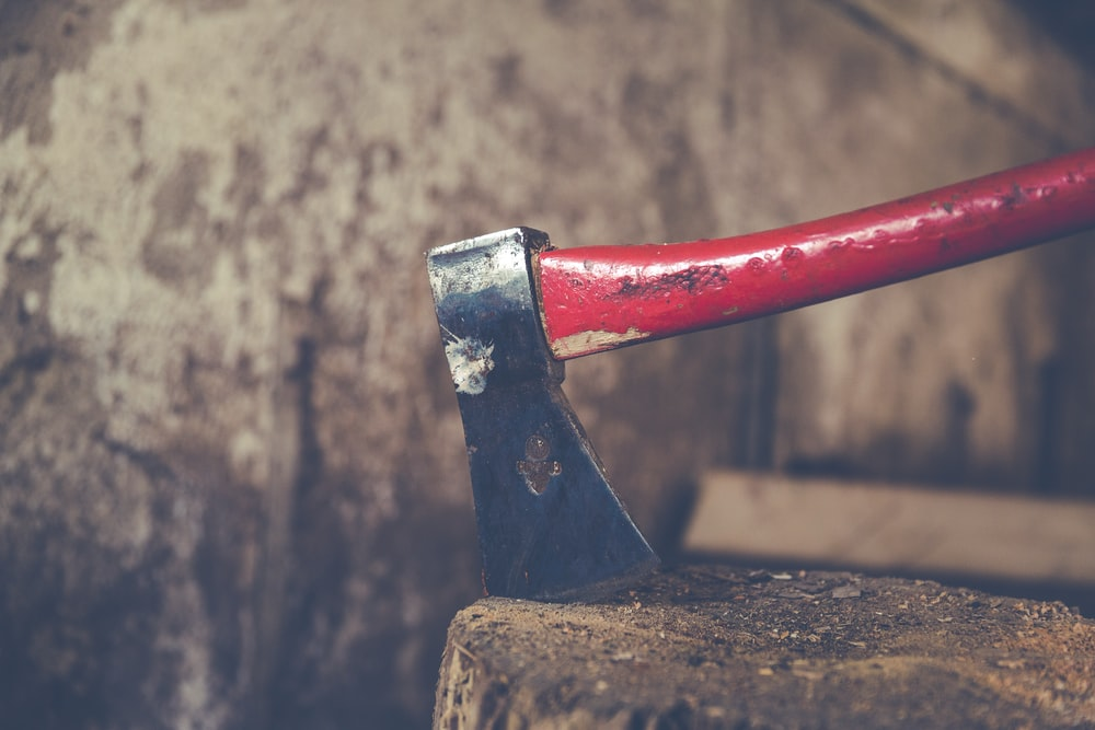 red and black axe on wood slab