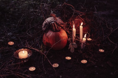 pumpkin between lighted candles spooky teams background