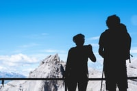silhouette photography of two person standing on top under clear blue sky