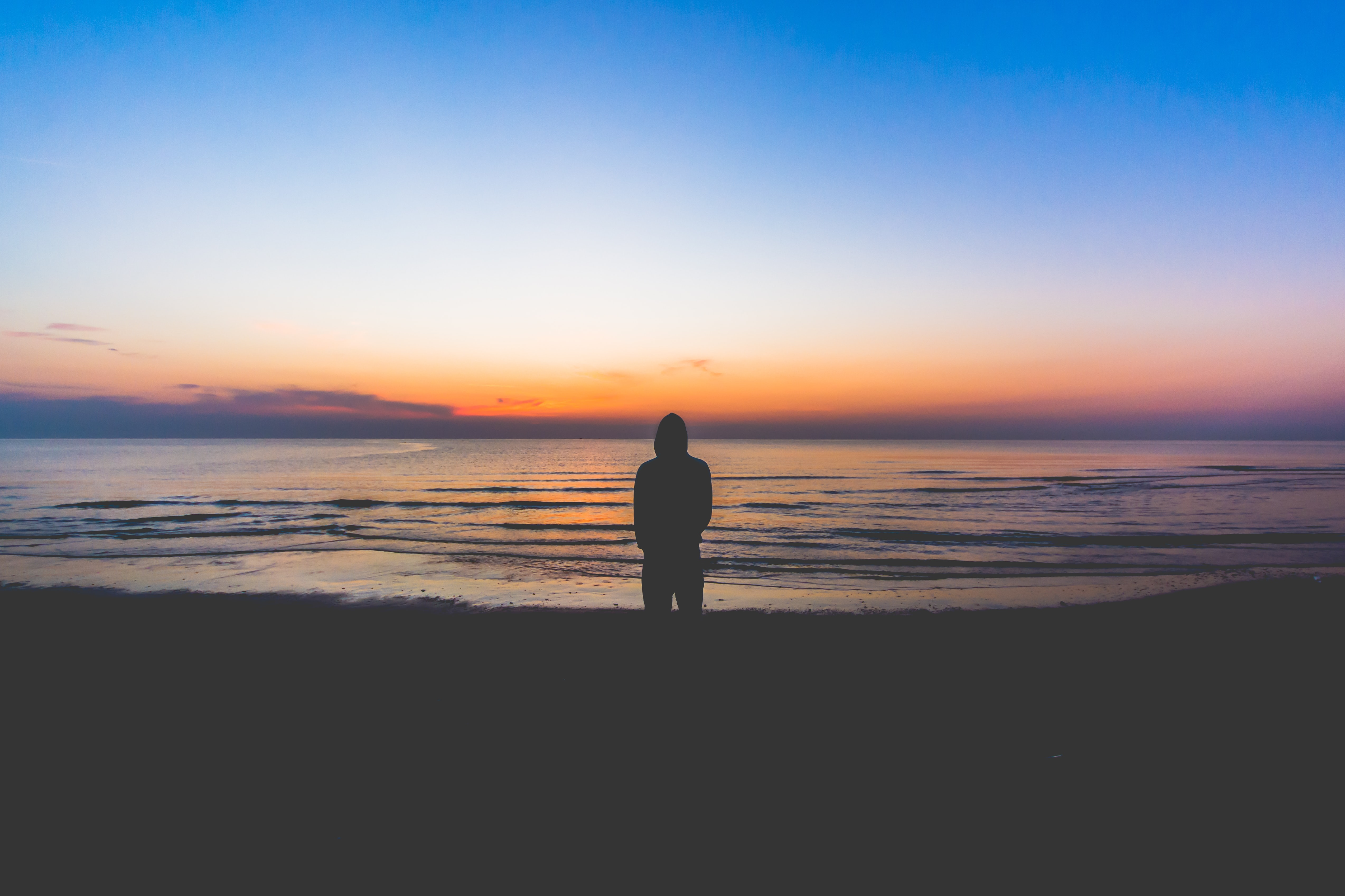 Silhouette of a person standing on the beach at the edge of rippling water watching the sunset