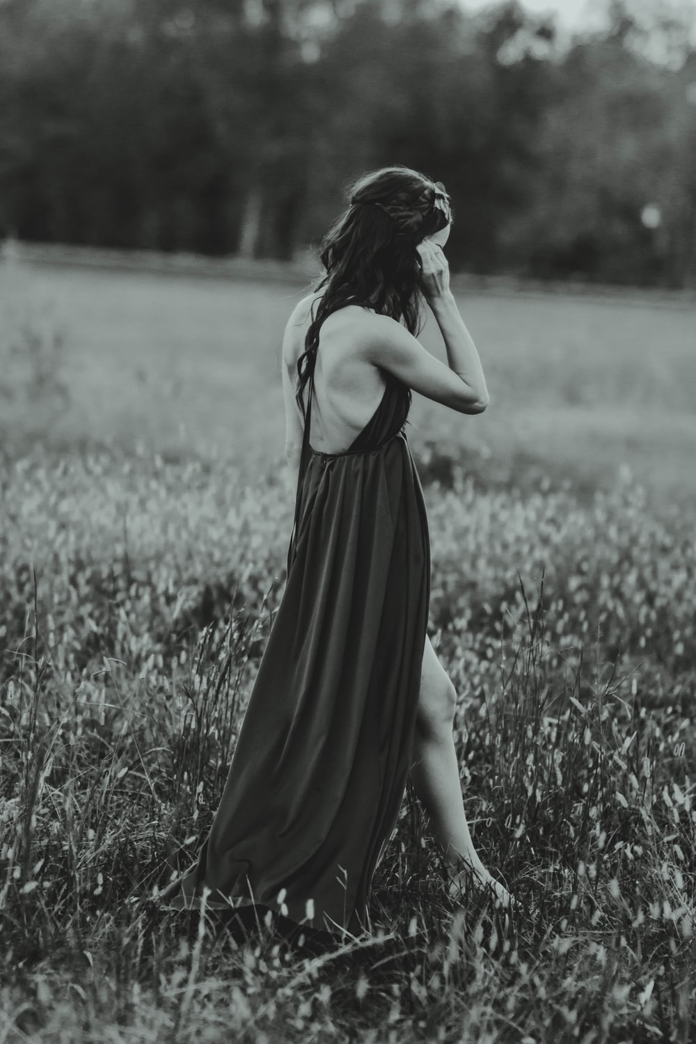 grayscale photography of woman wearing dress on grass field while standing