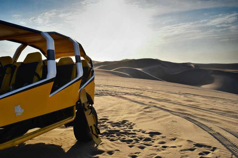 yellow and white UTV on desert
