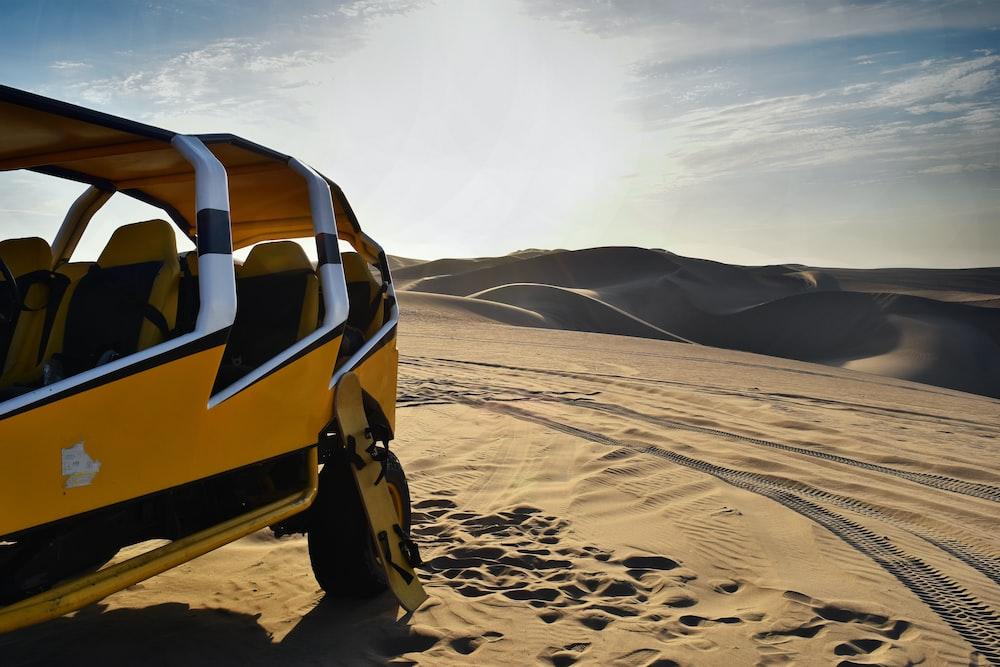 yellow and white UTV on desert