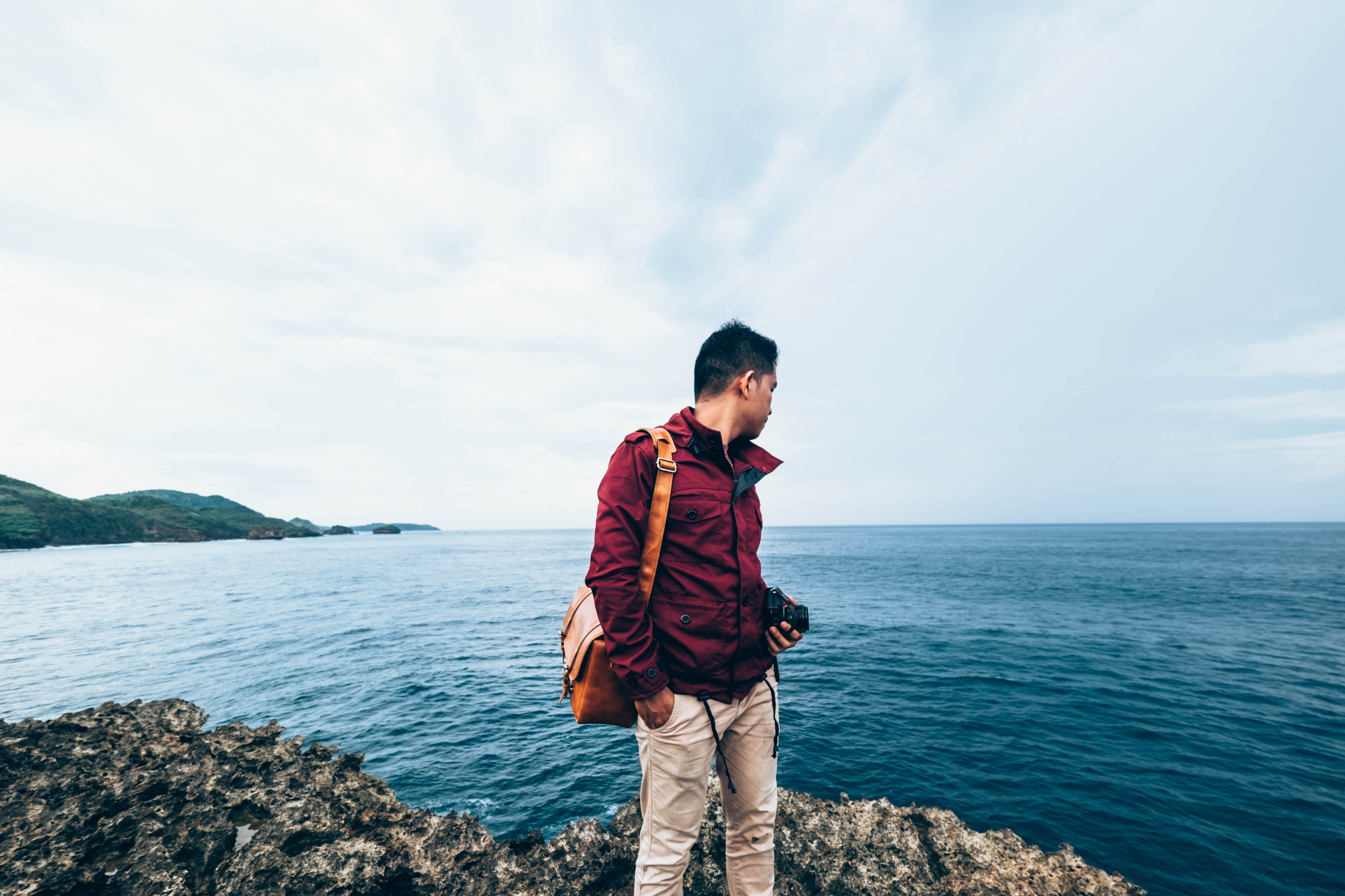 man wearing red zip-up jacket standing on top of rocky cliff beside body of water during daytime