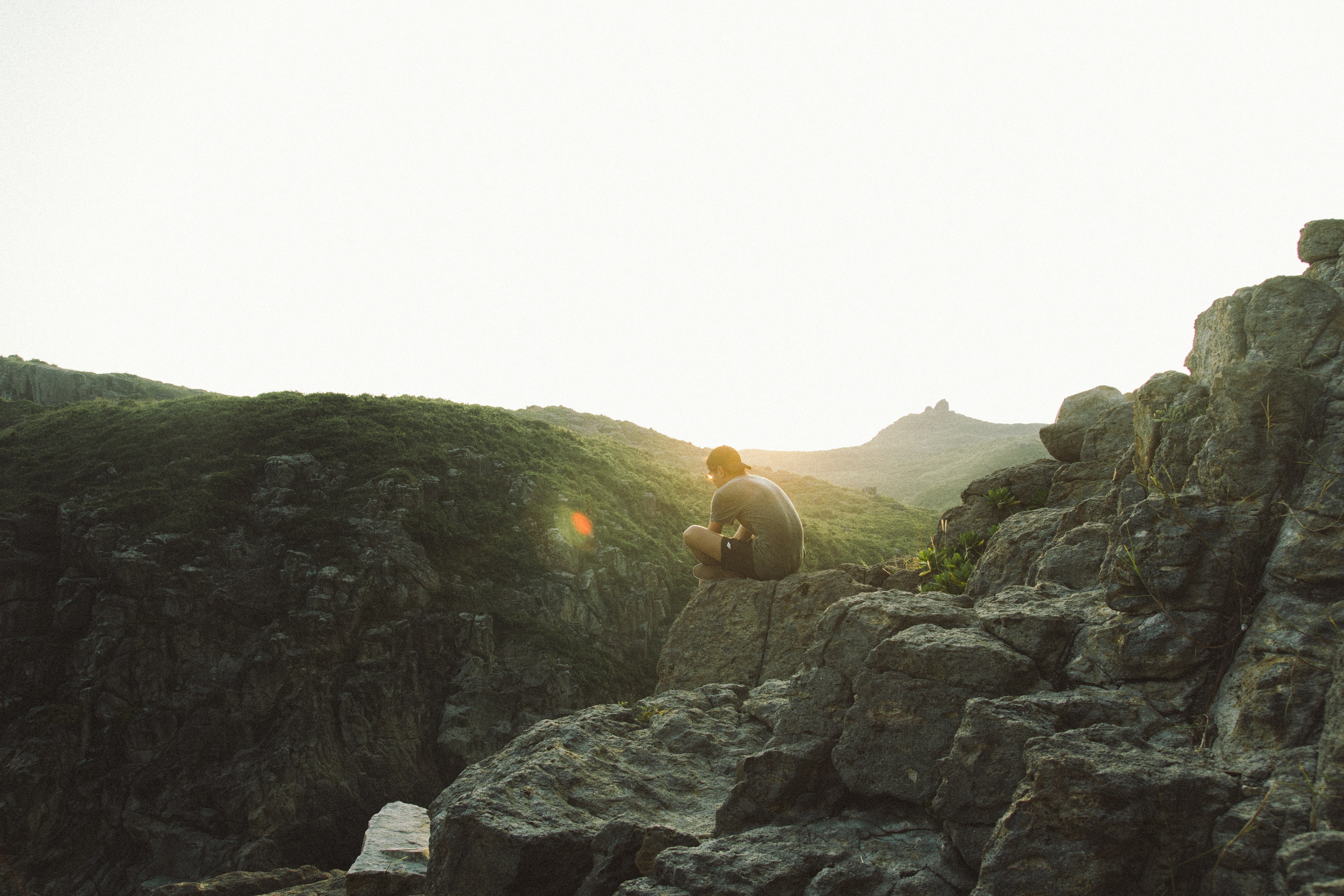 Man sitting on the stone edge of a mountain in Hong Kong during sunset