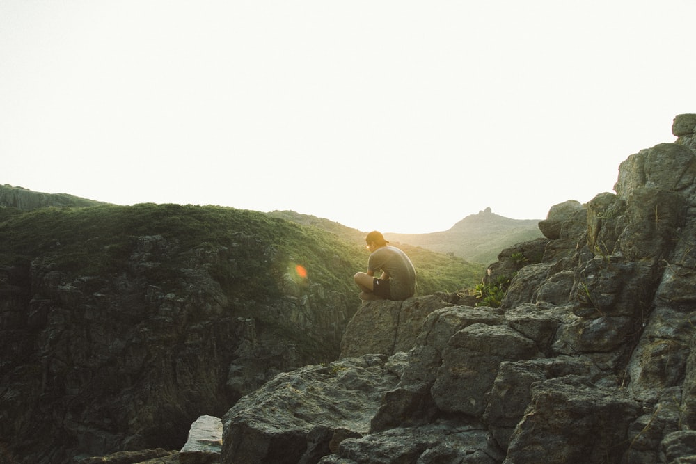 man sitting near cliff during sunrise