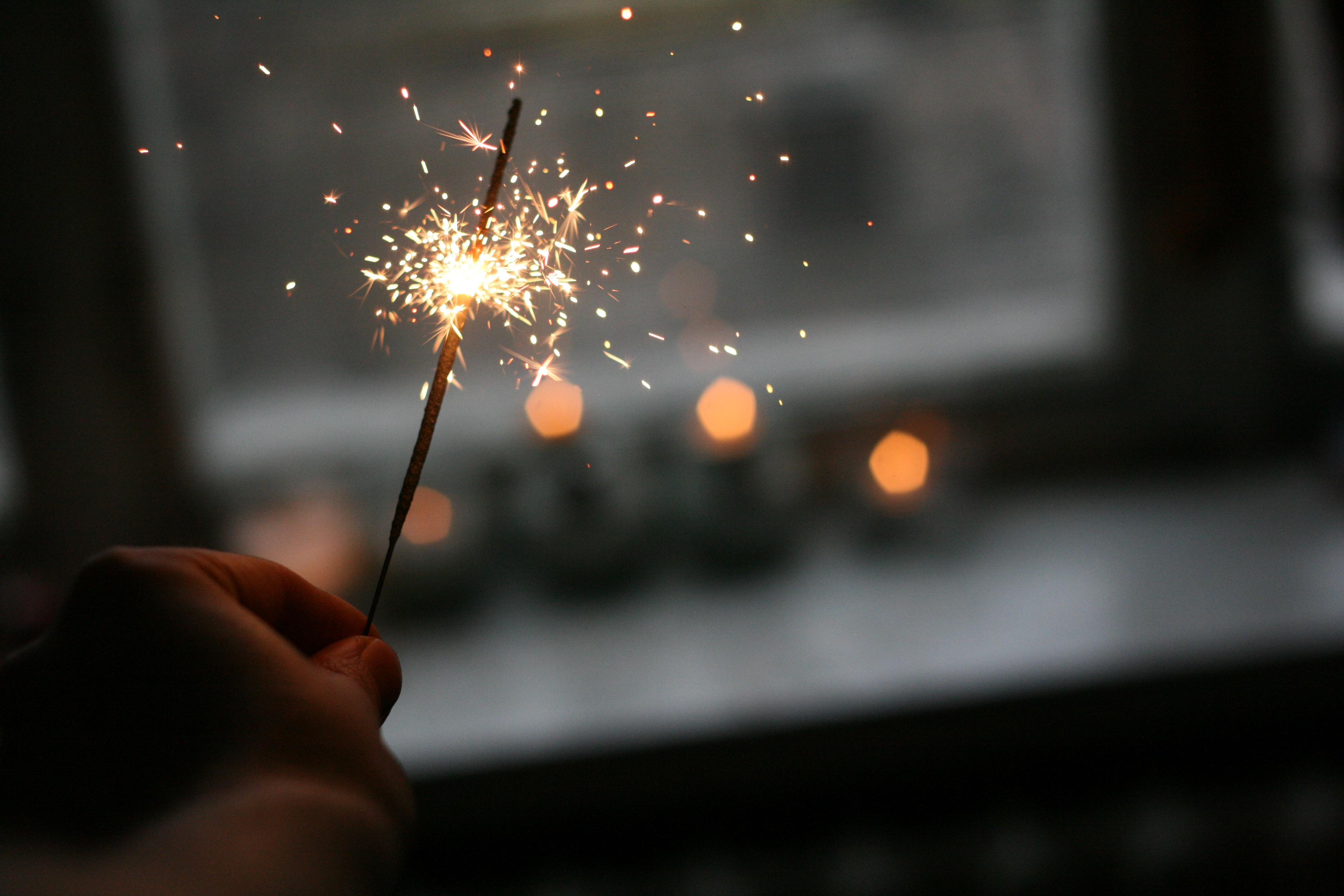 A person holding a sparkler near a window