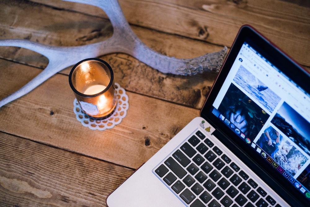 MacBook Pro beside votive candle