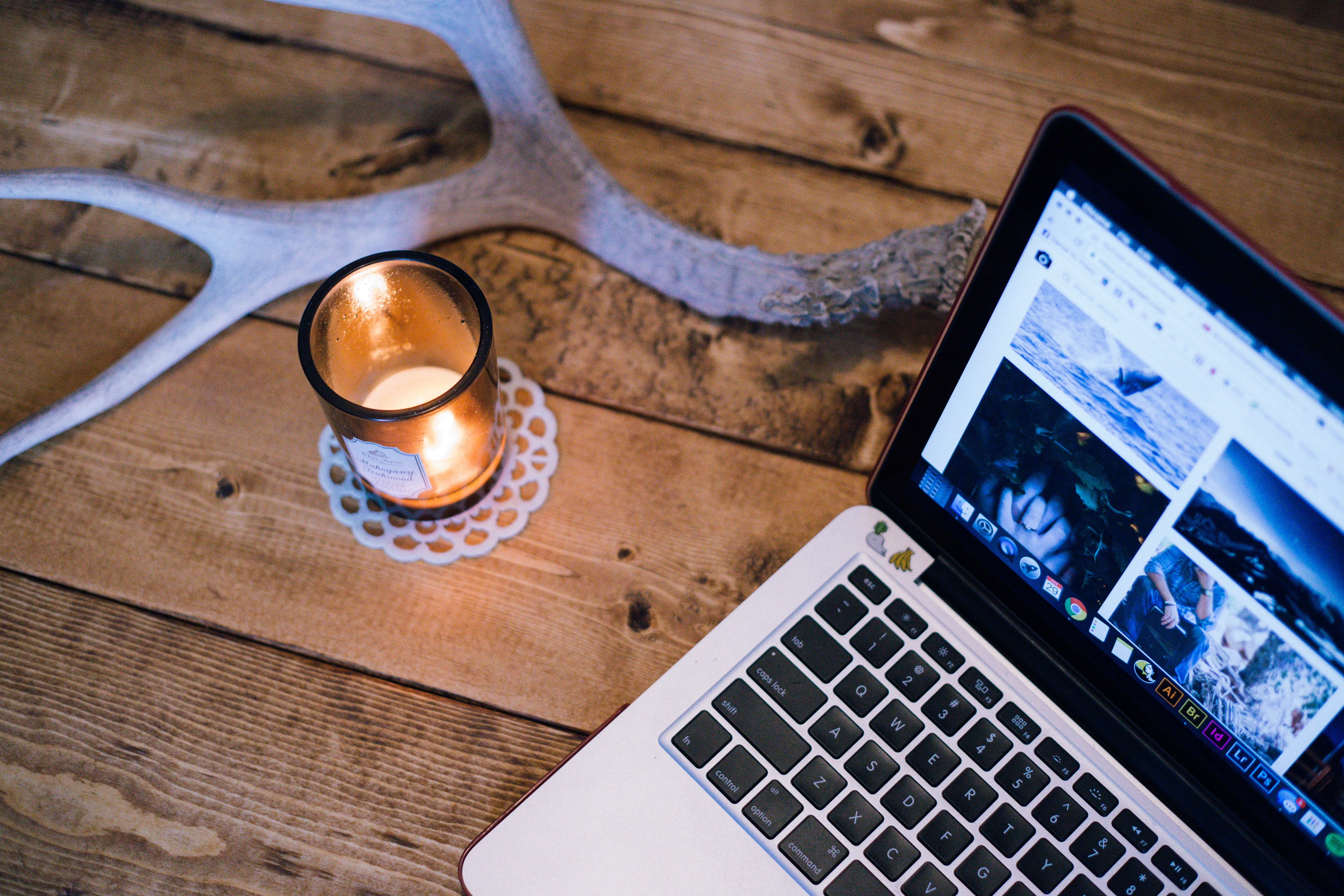 A lit candle and an antler on a table next to a laptop
