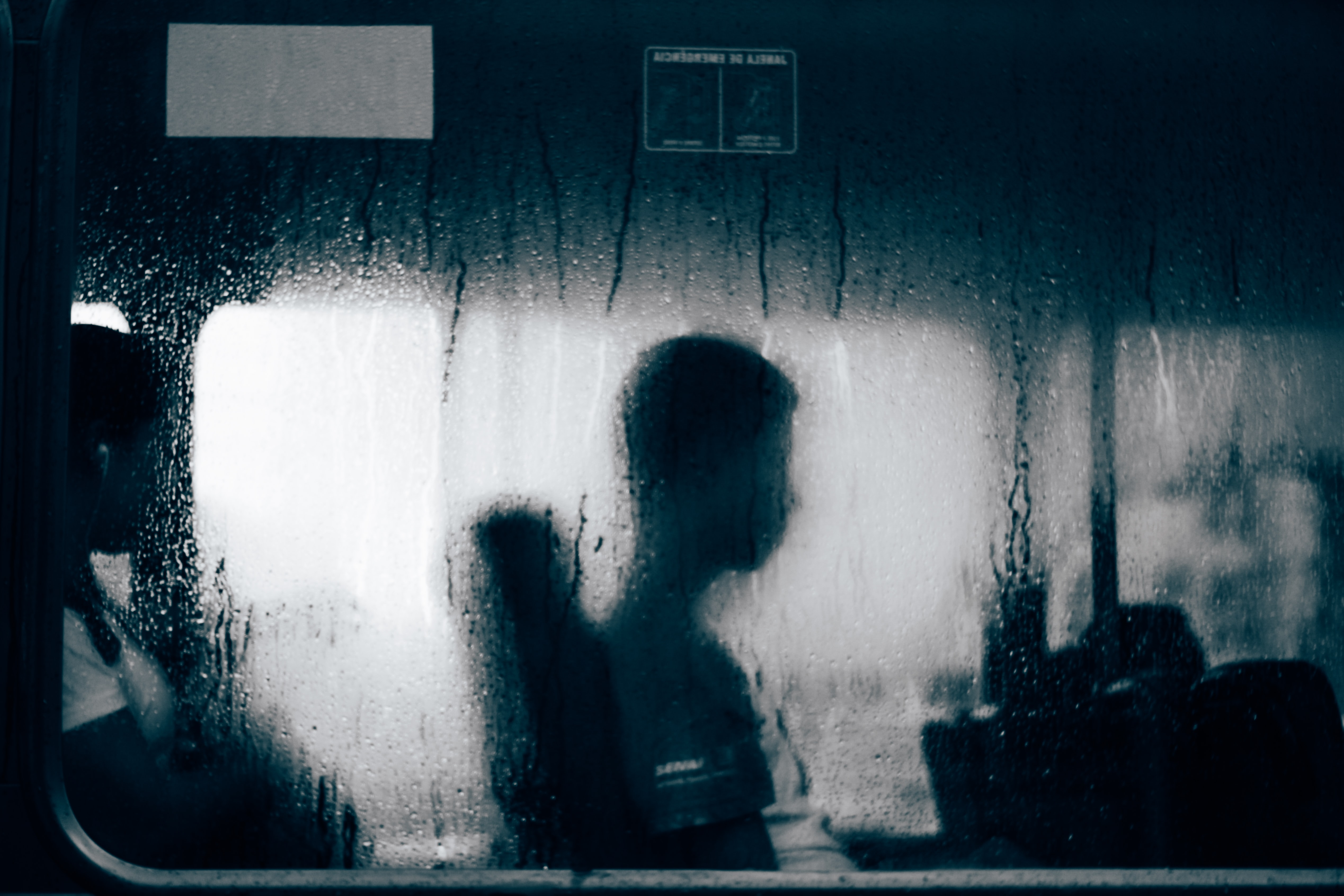Profile silhouette of person sitting near window with rain water on it