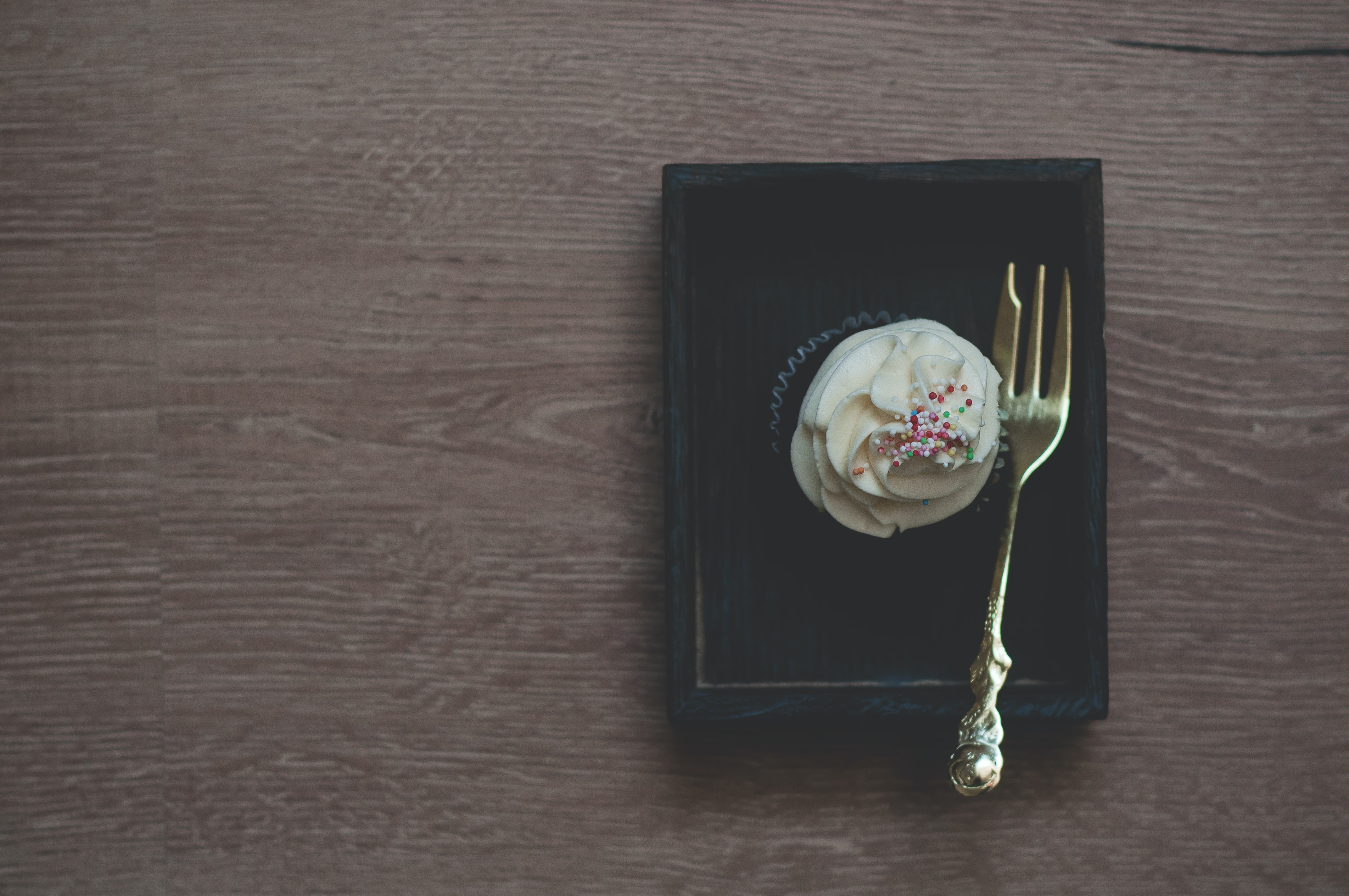 brass-colored pastry fork on black box beside cupcake with white frosting