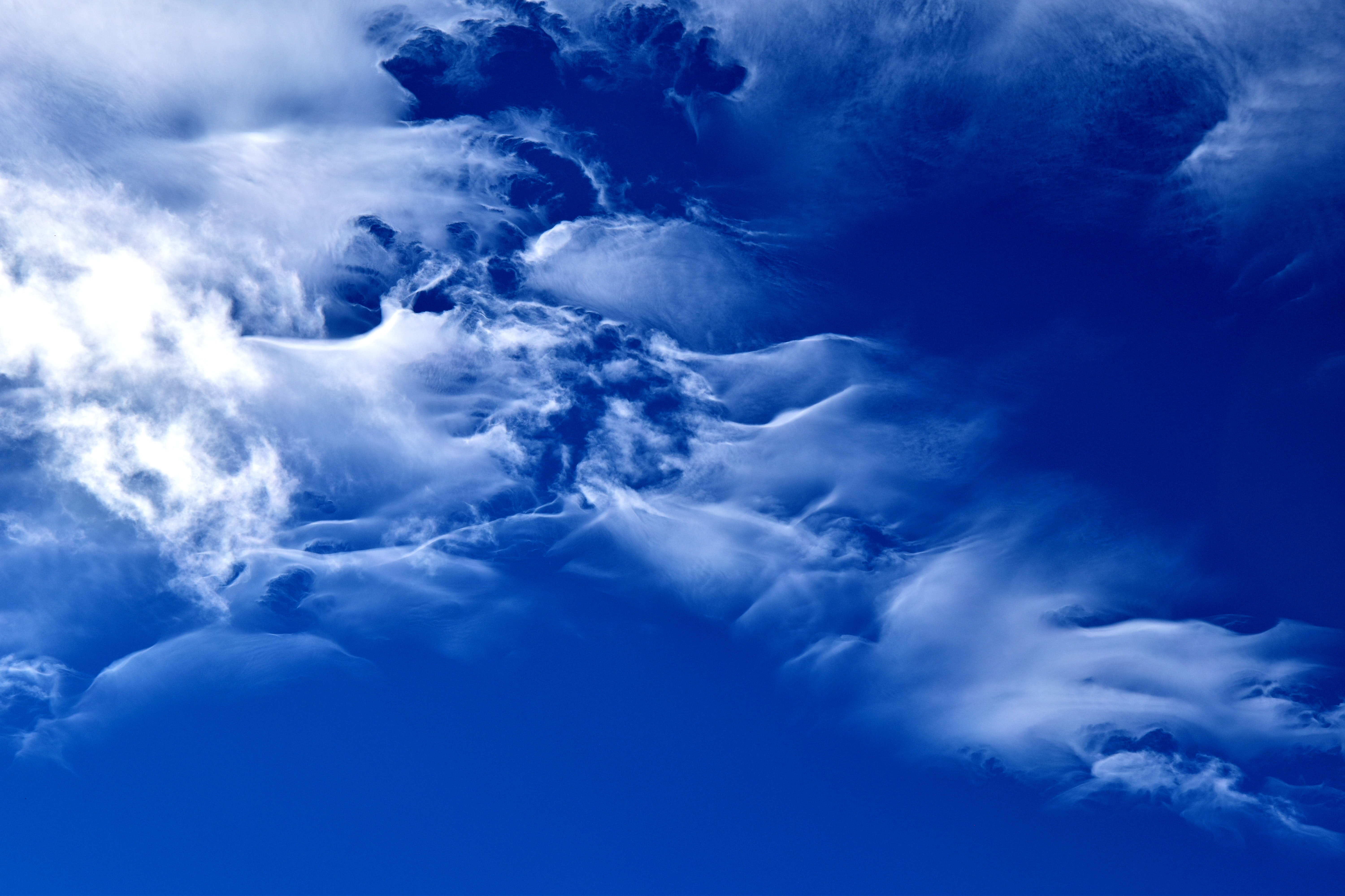 The blue sky above a playful veil of clouds