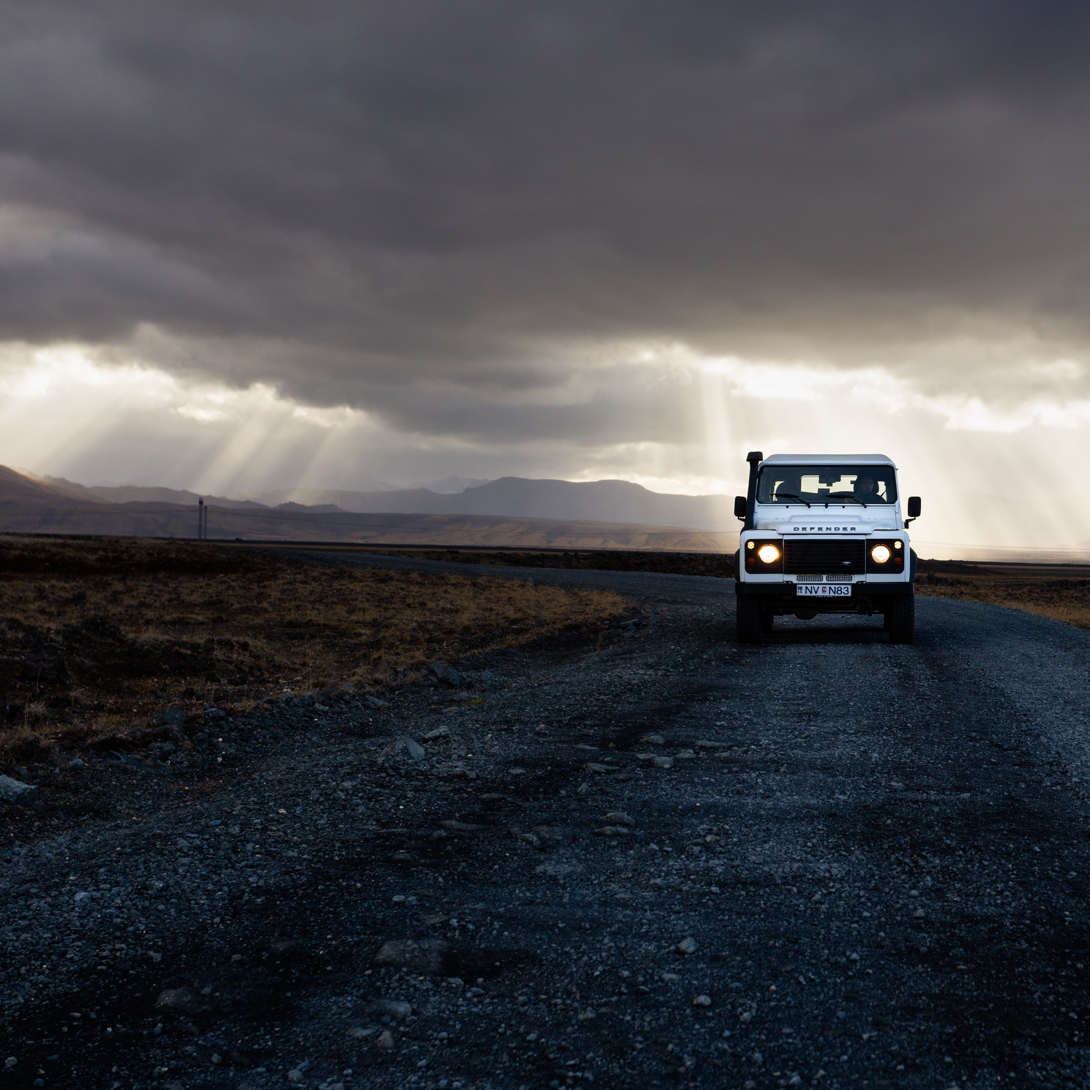 A white 4x4 truck driving down the road while rays of sun peek through the clouds in Iceland