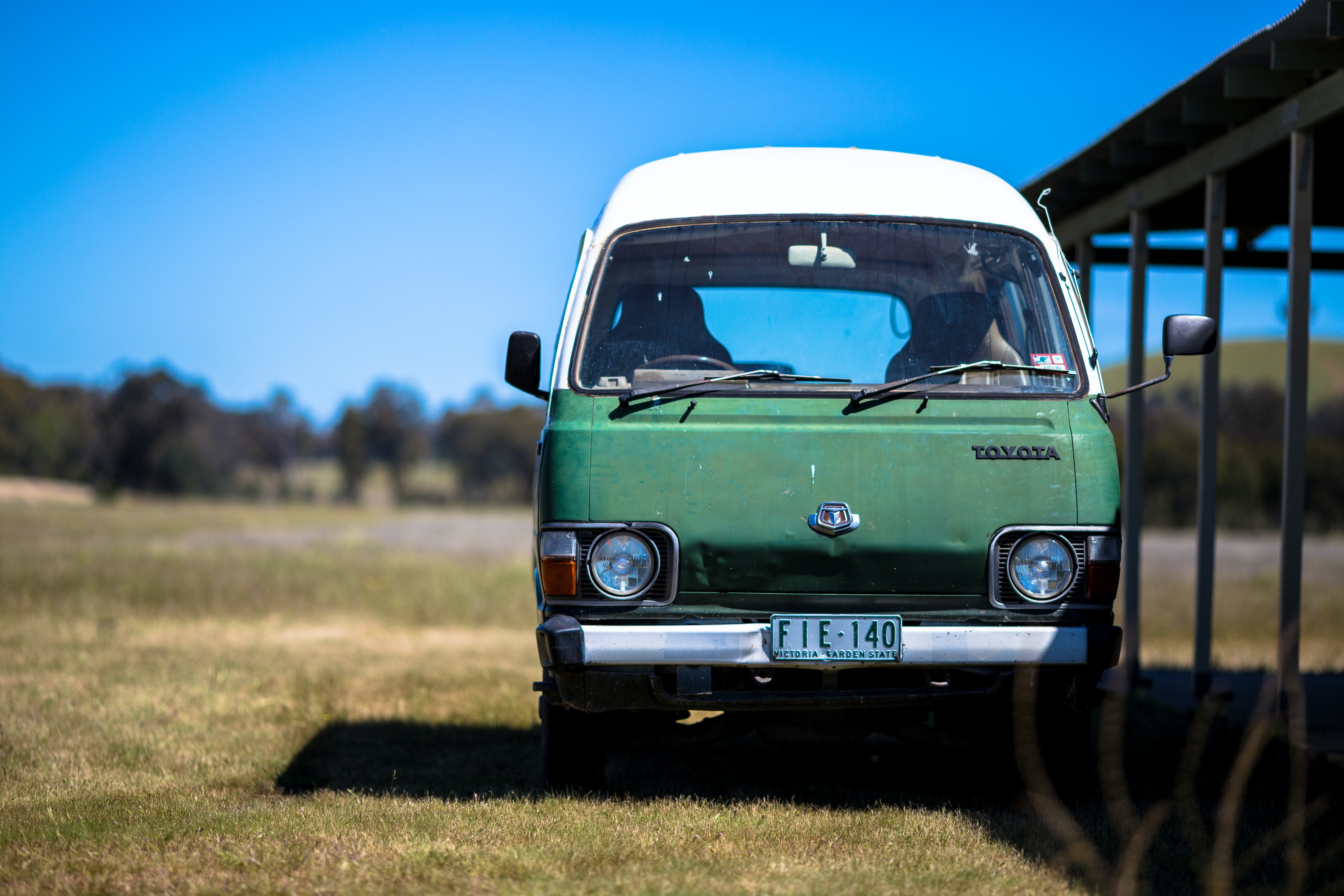 A vintage two tone minivan in the middle of a green field of grass and a blue sky.