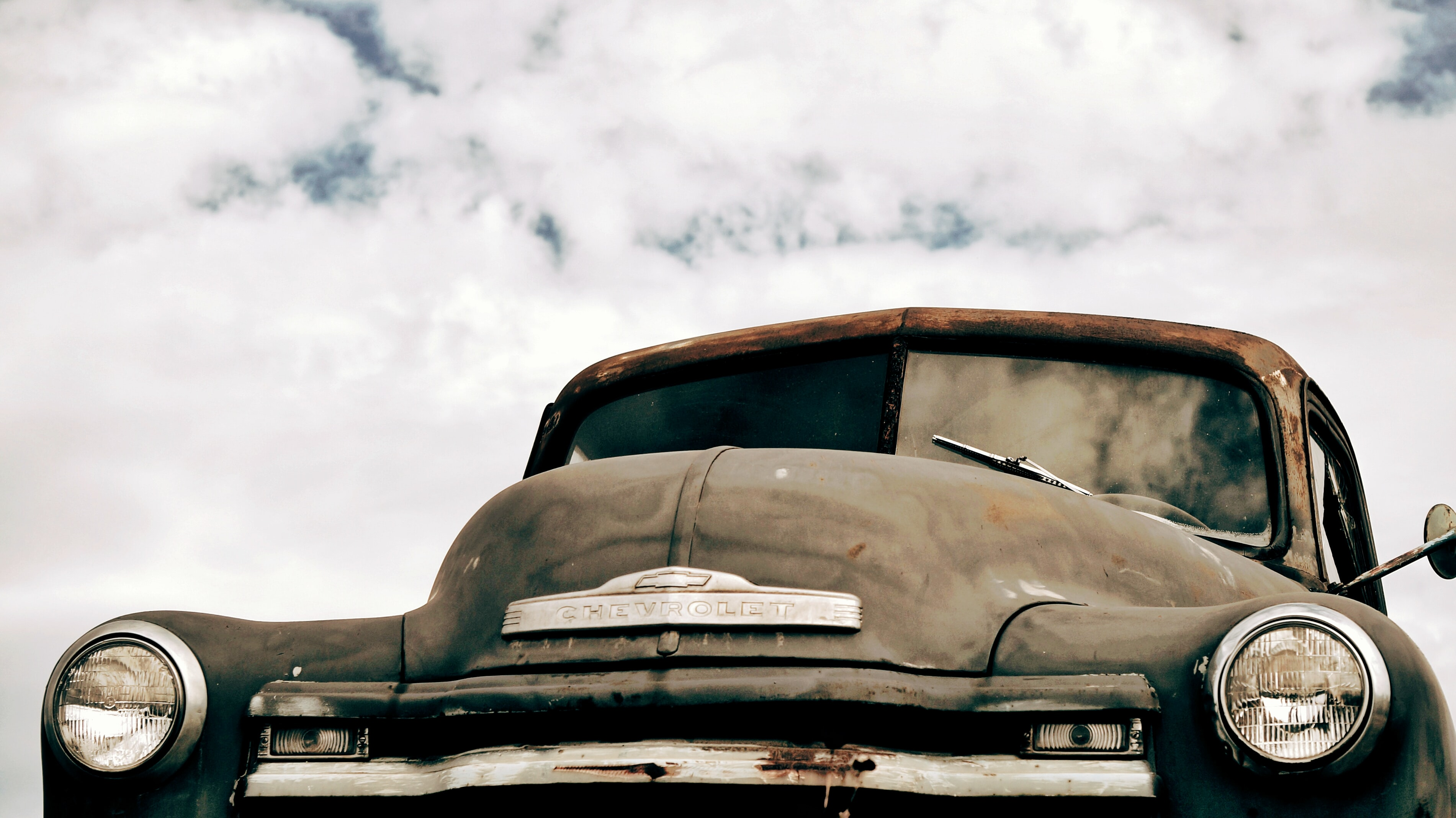 Front view of a rusted vintage car prominently featuring the hood.