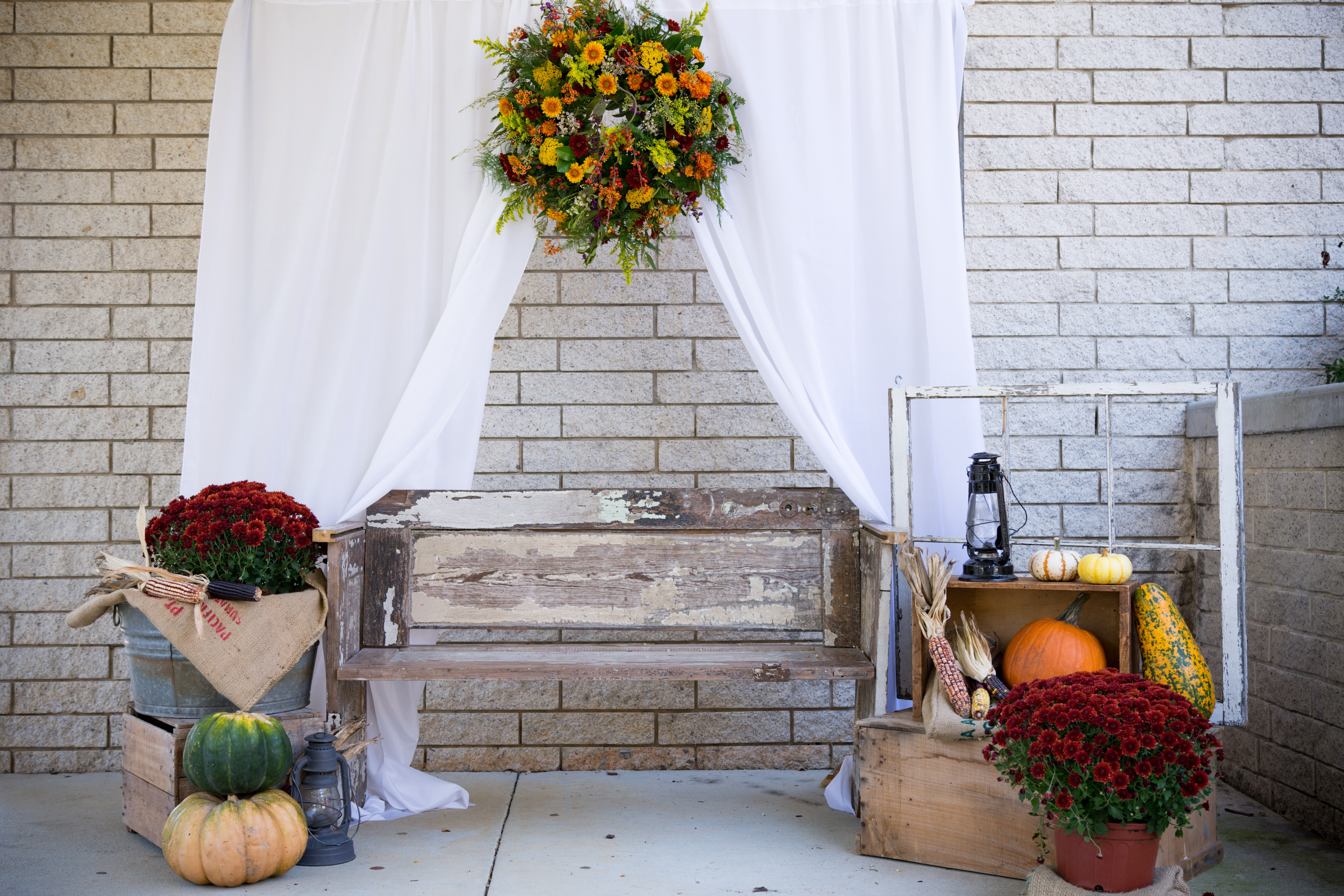 A wooden bench surrounded by a white drape with a wreath, red flowers in pots and various gourds