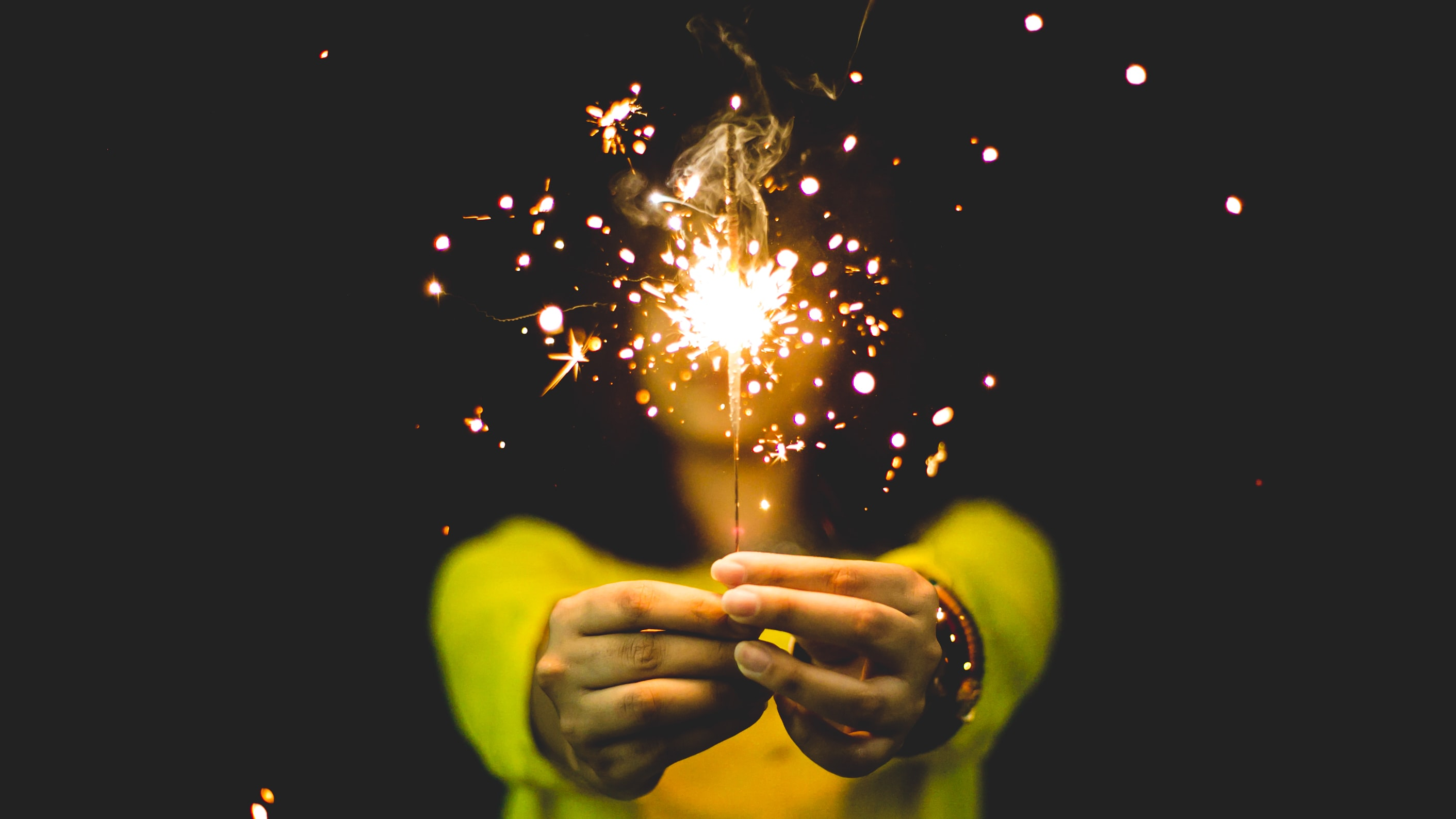 A person holding a lit sparkler in front of them