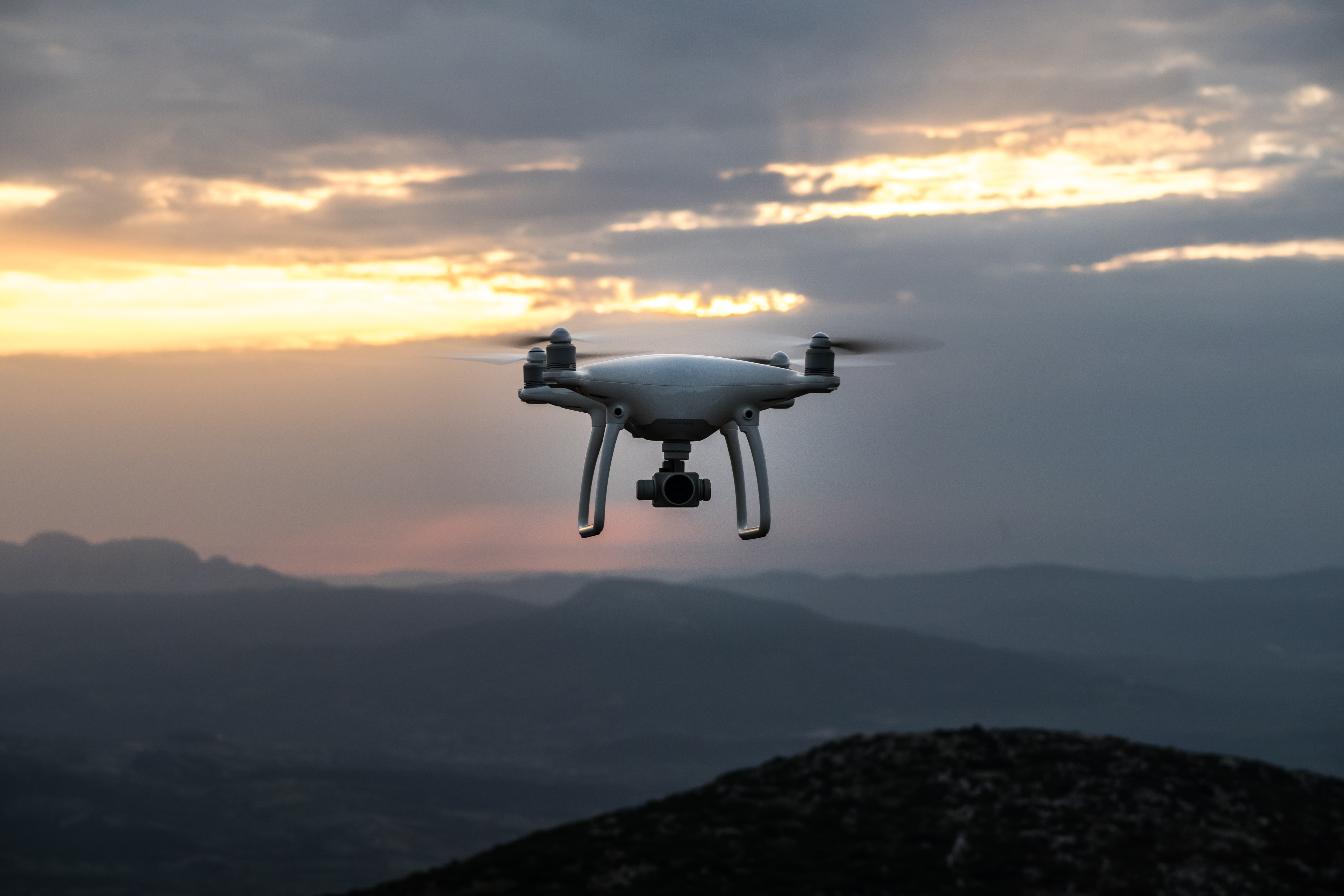 An aerial shot of a drone in flight over hilly terrain in Greece during a cloud covered sunrise-or-sunset