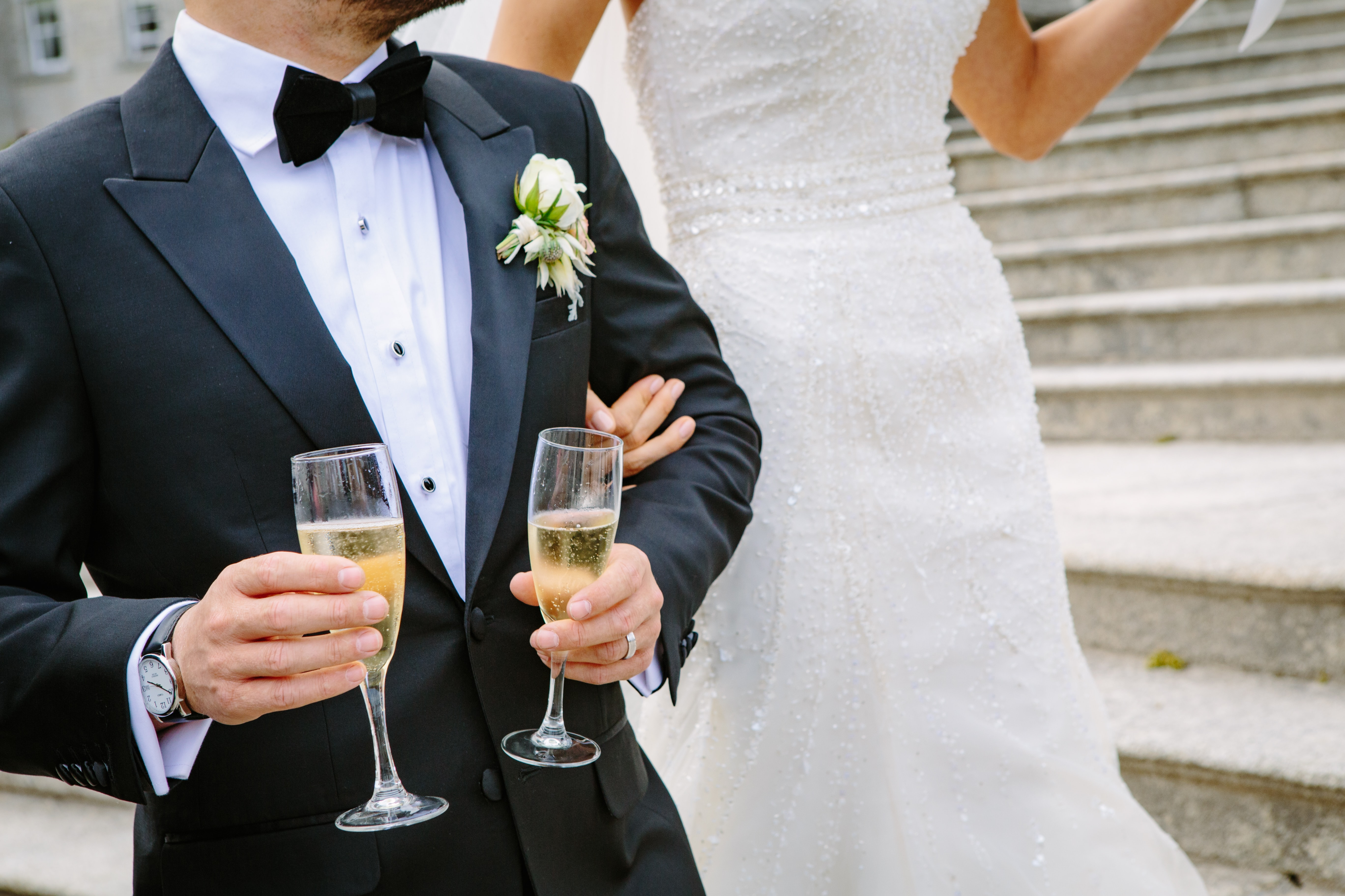 A groom holding two champagne glasses next to a bride in her wedding dress