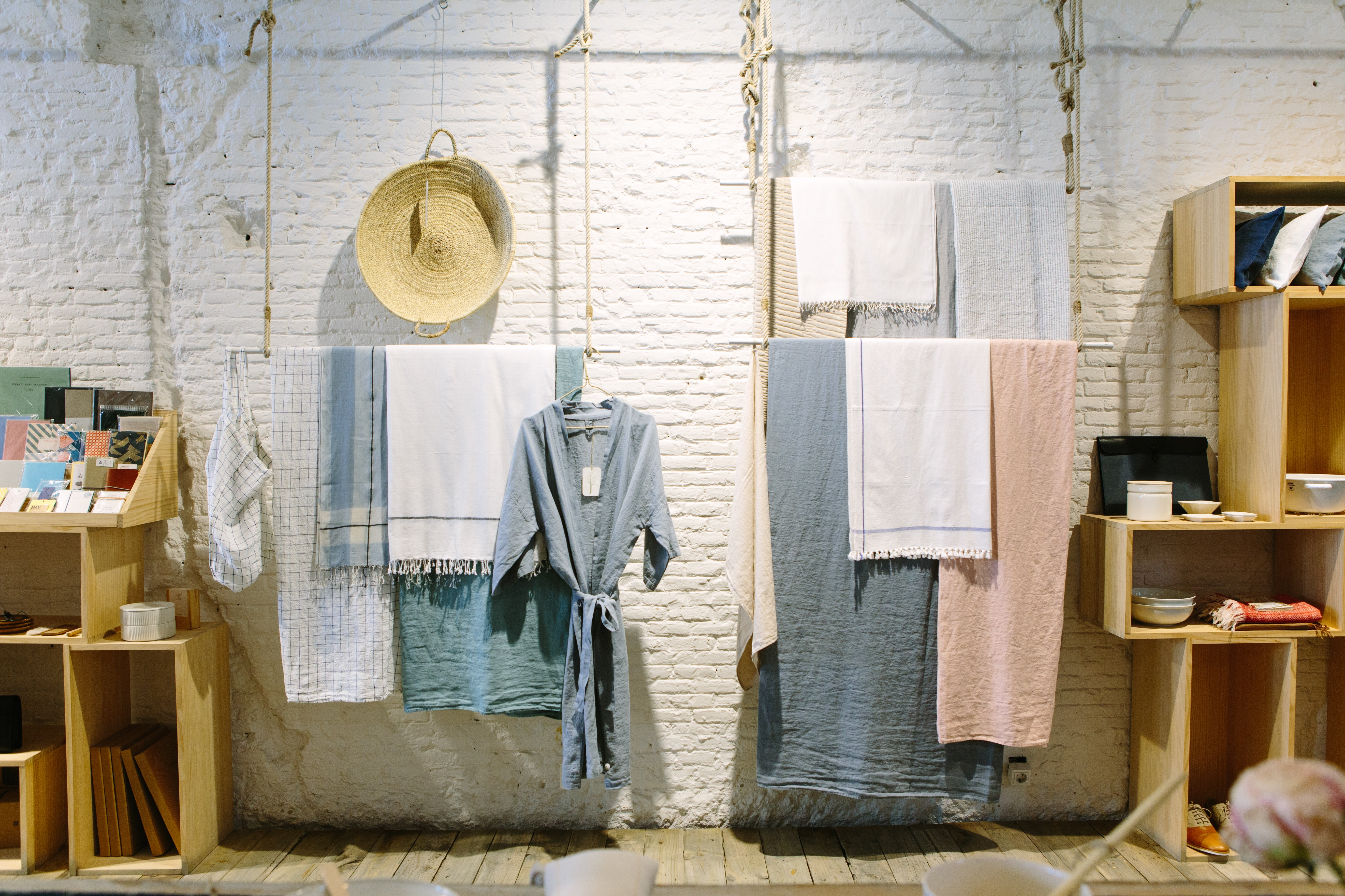 Towels and clothes hanging from a ceiling in an artistic interior