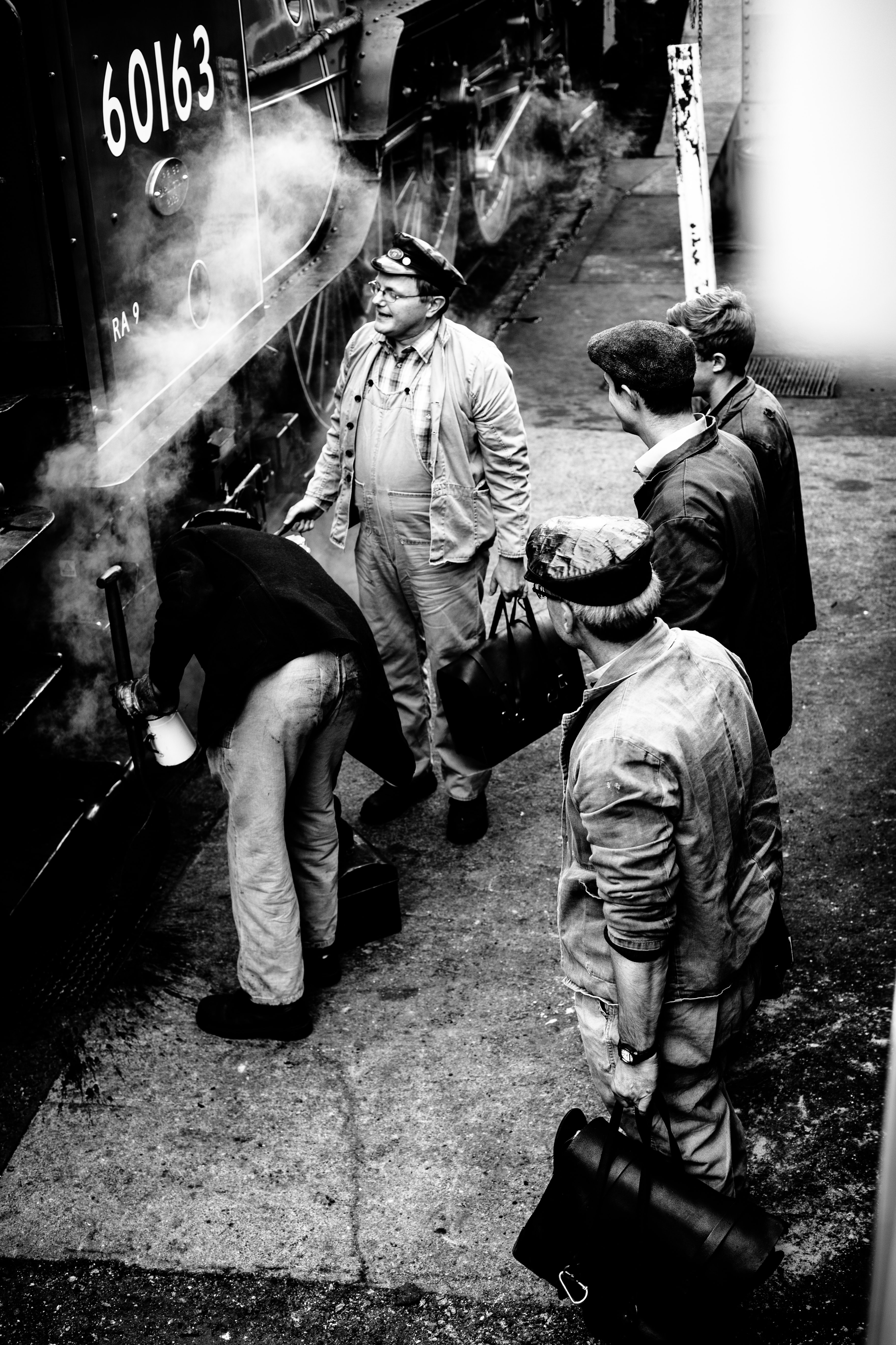 Black-and-white shot of train engineers standing by the steam train at Severn Valley Railway.