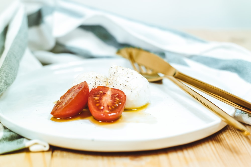 sliced tomato and mozzarella cheese on white plate beside brass-colored knife and fork