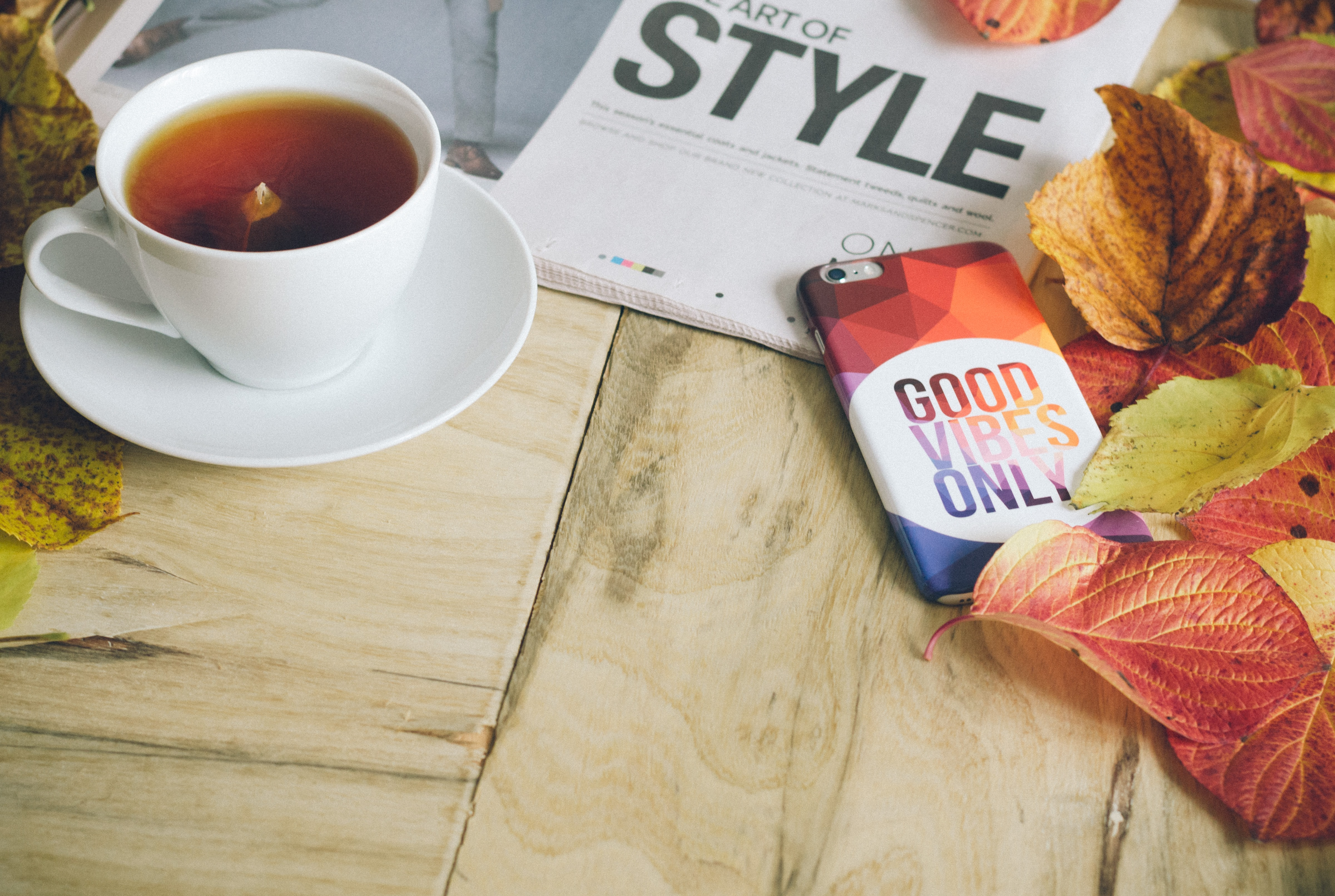 An iPhone in a colorful case next to a newspaper, a cup of coffee and orange autumn leaves