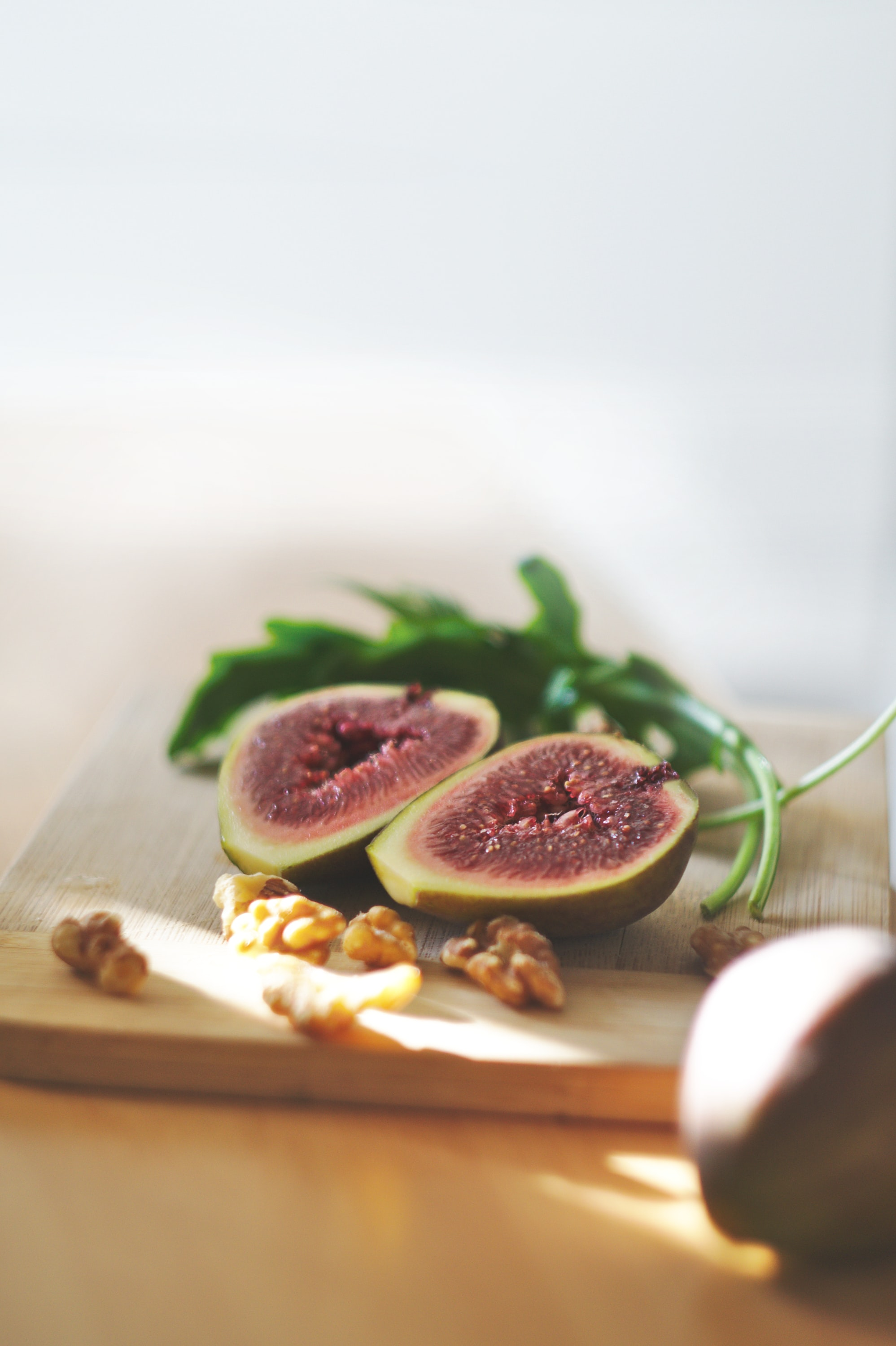 Cutting board with a fig fruit cut in half, a sprig of arugula, and walnuts
