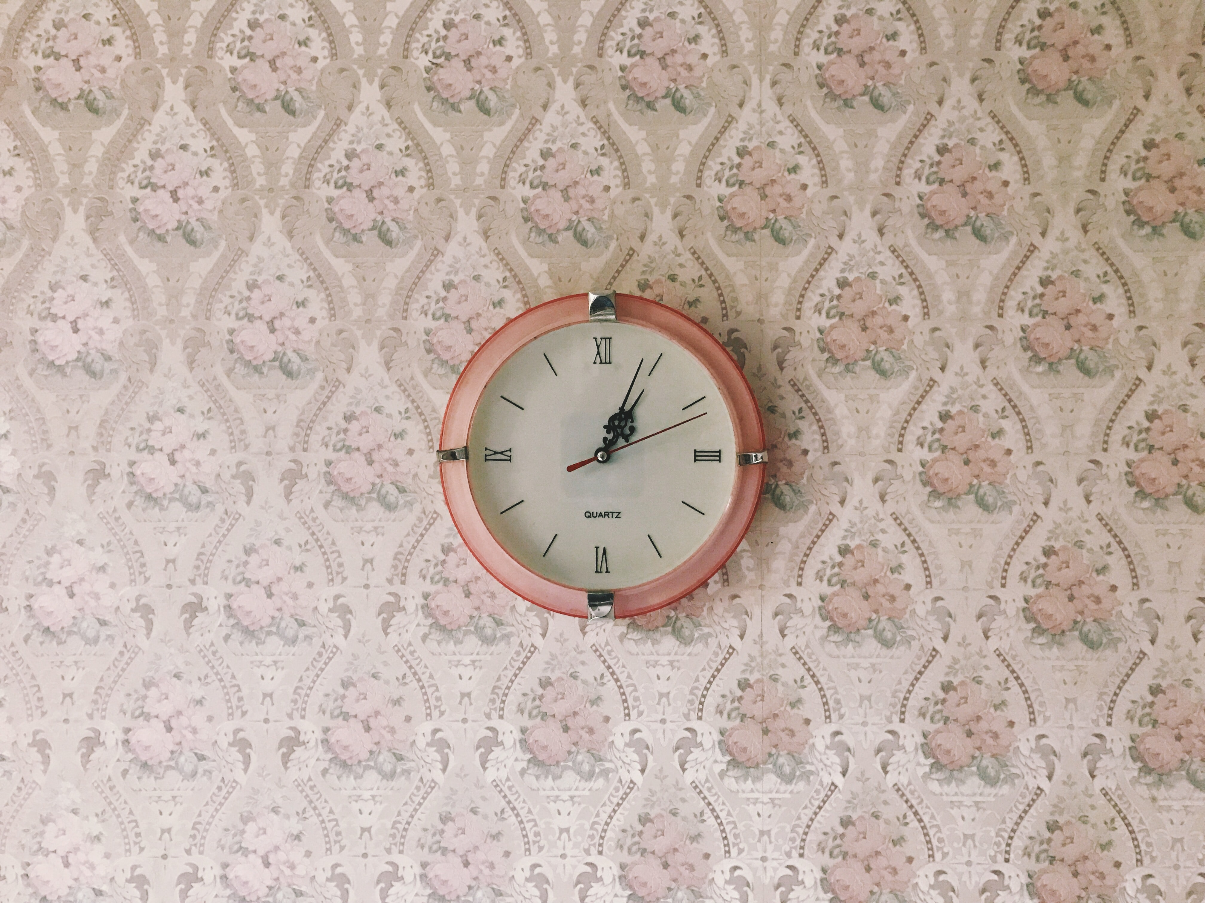 A pink clock on a pink floral patterned wall in Williamson