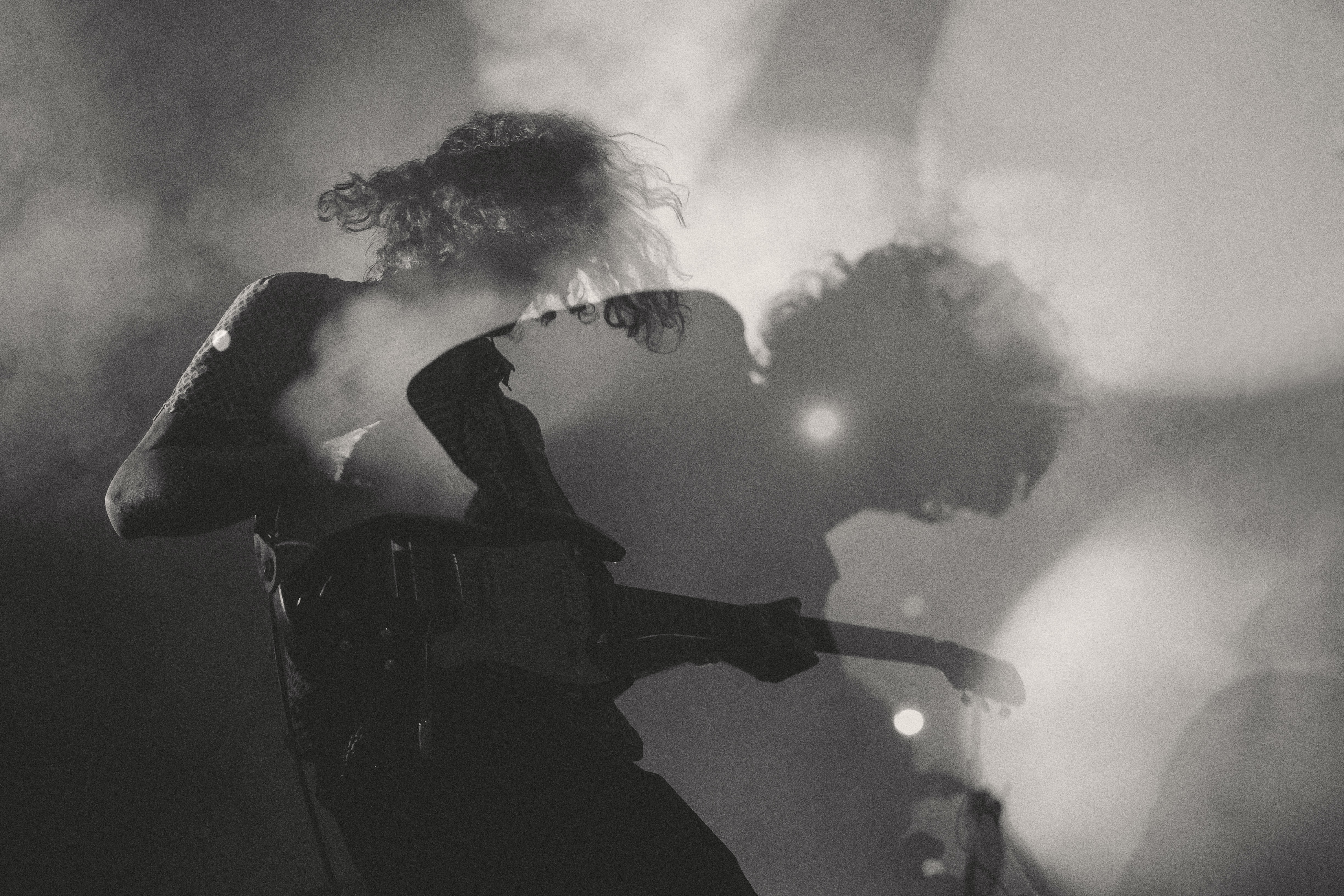 A black-and-white shot of a man playing electric guitar in double exposure