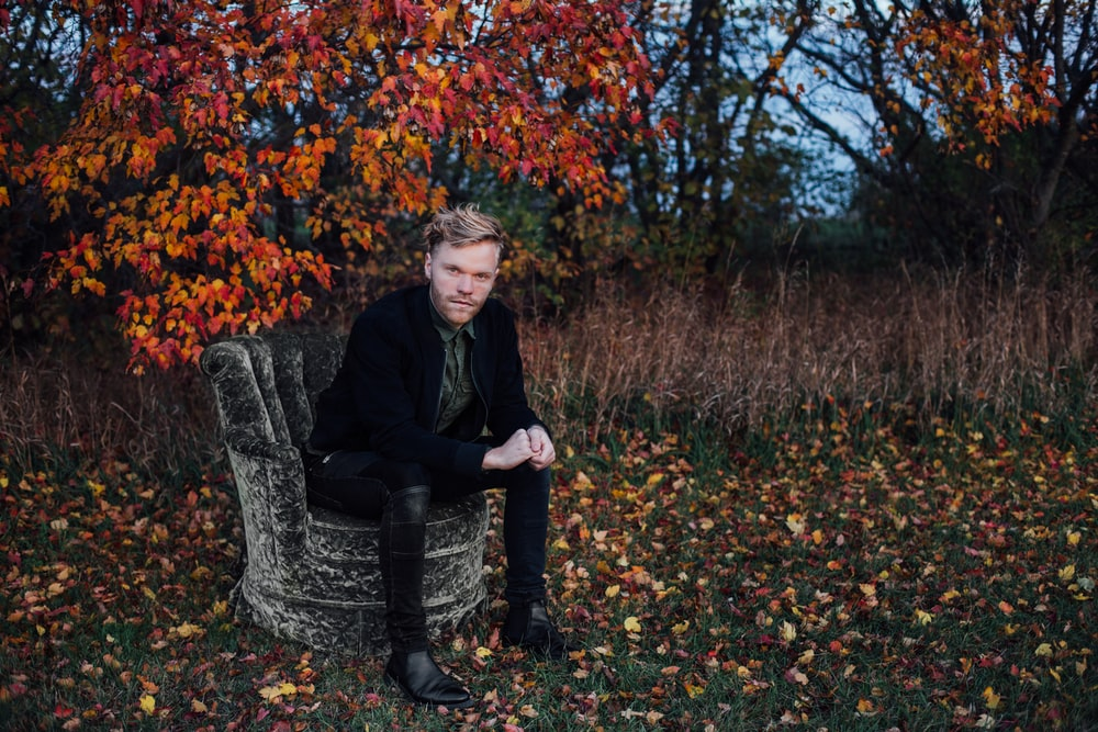 man wearing black suit sits on black concrete chair beside brown tree