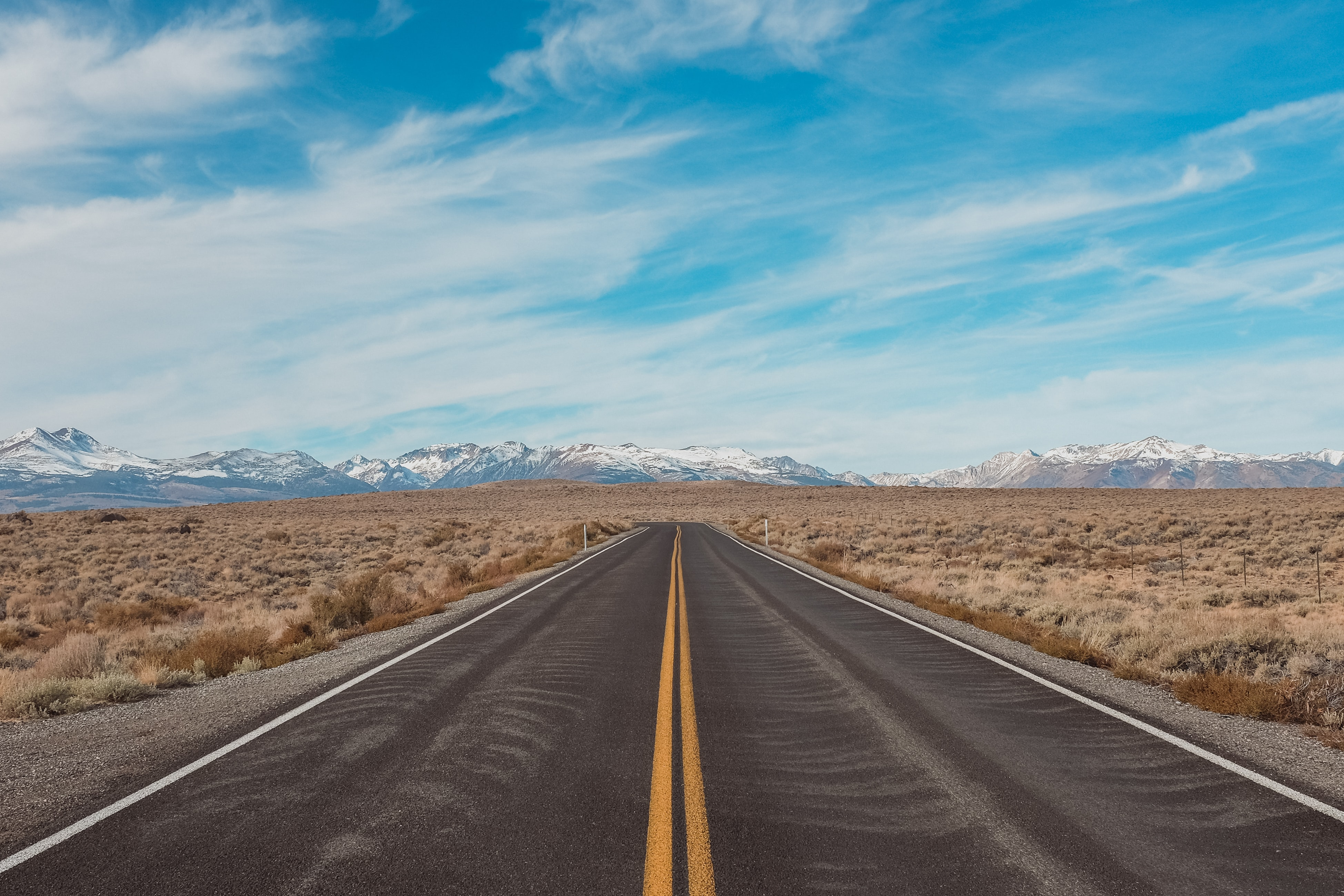 A long empty asphalt road through dry plains with snowy mountains on the horizon