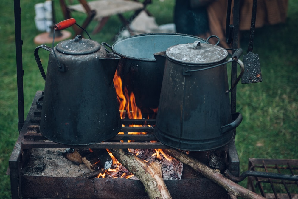 two kettles and one pot on top of fire