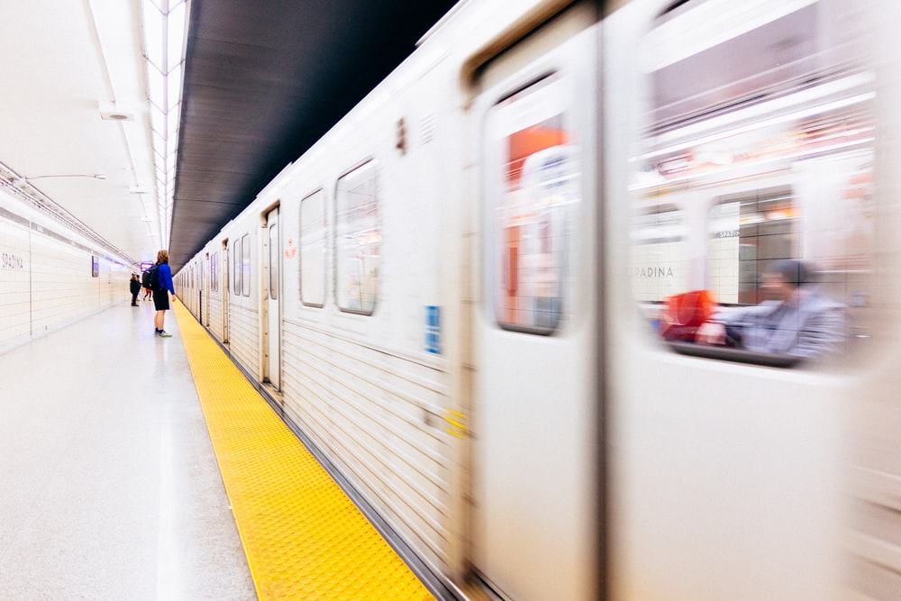 selective focus photography of person standing on train station